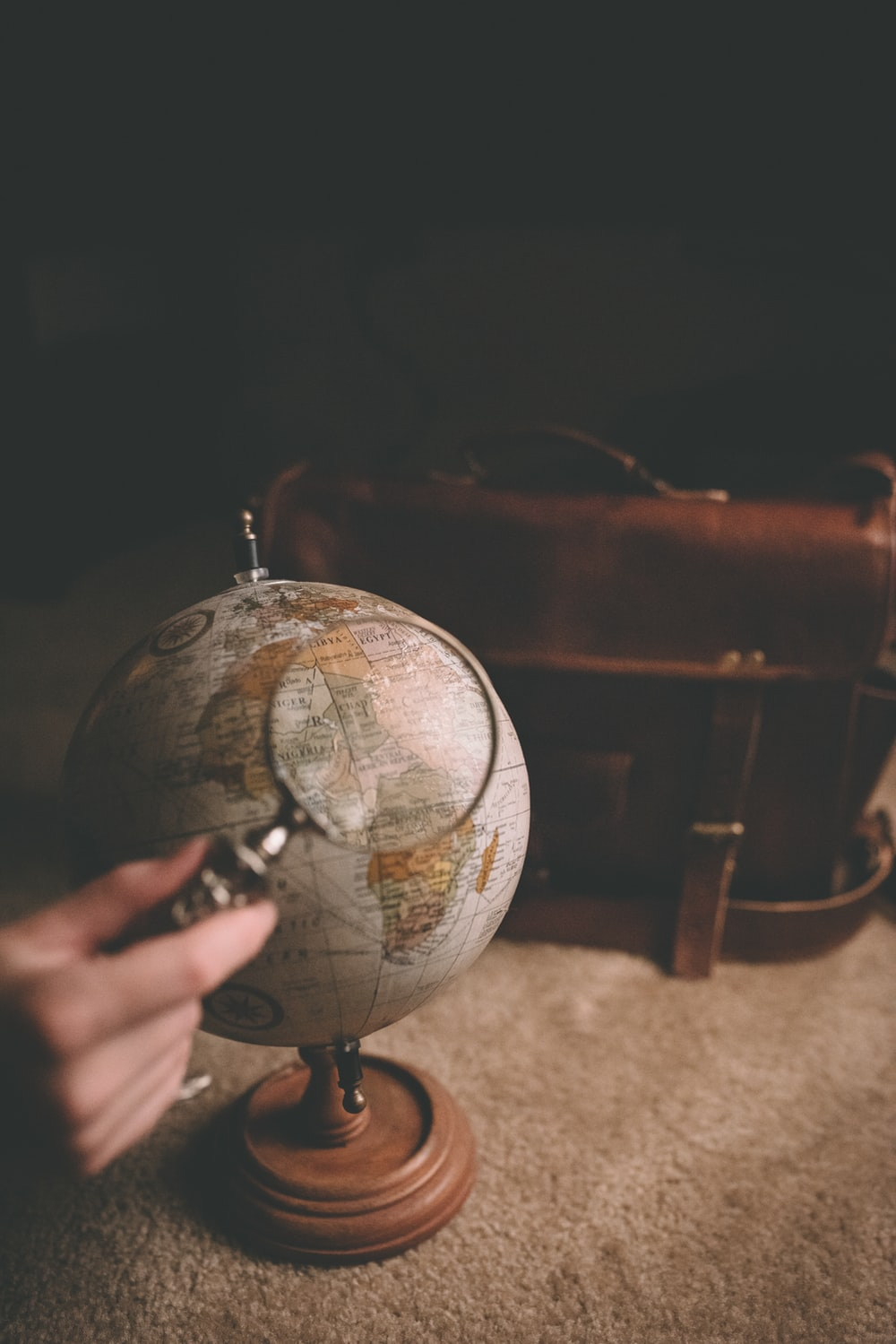 person holding magnifying glass near desk globe