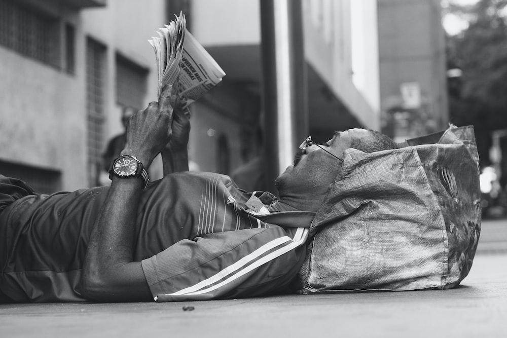 man lying on sidewalk reading newspaper