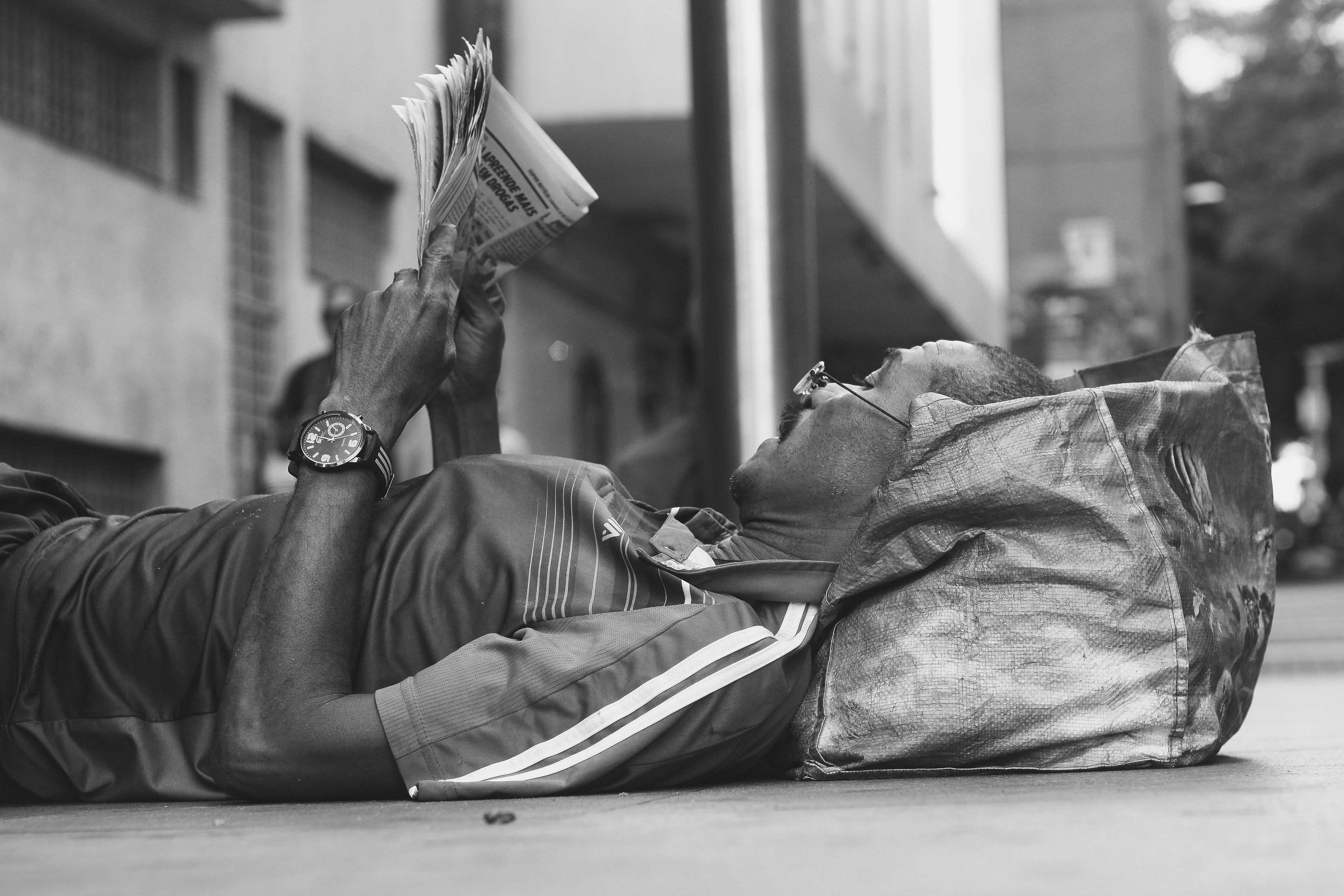 Black and white shot of man in glasses lying with head on bag reading newspaper