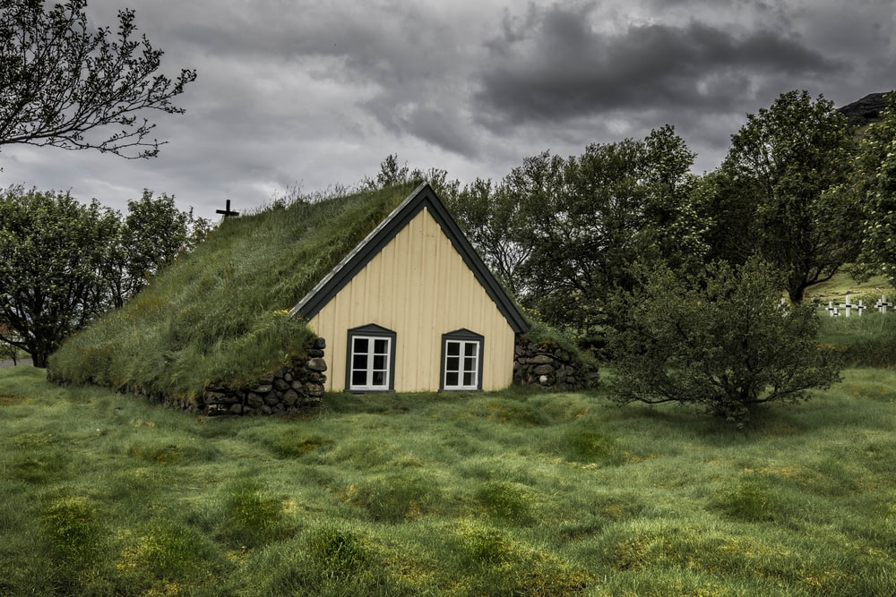 brown wooden house surrounded with green trees under gray clouds