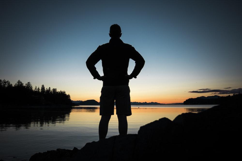 黄金の時間の間に水の体の近くに立っている人のシルエット