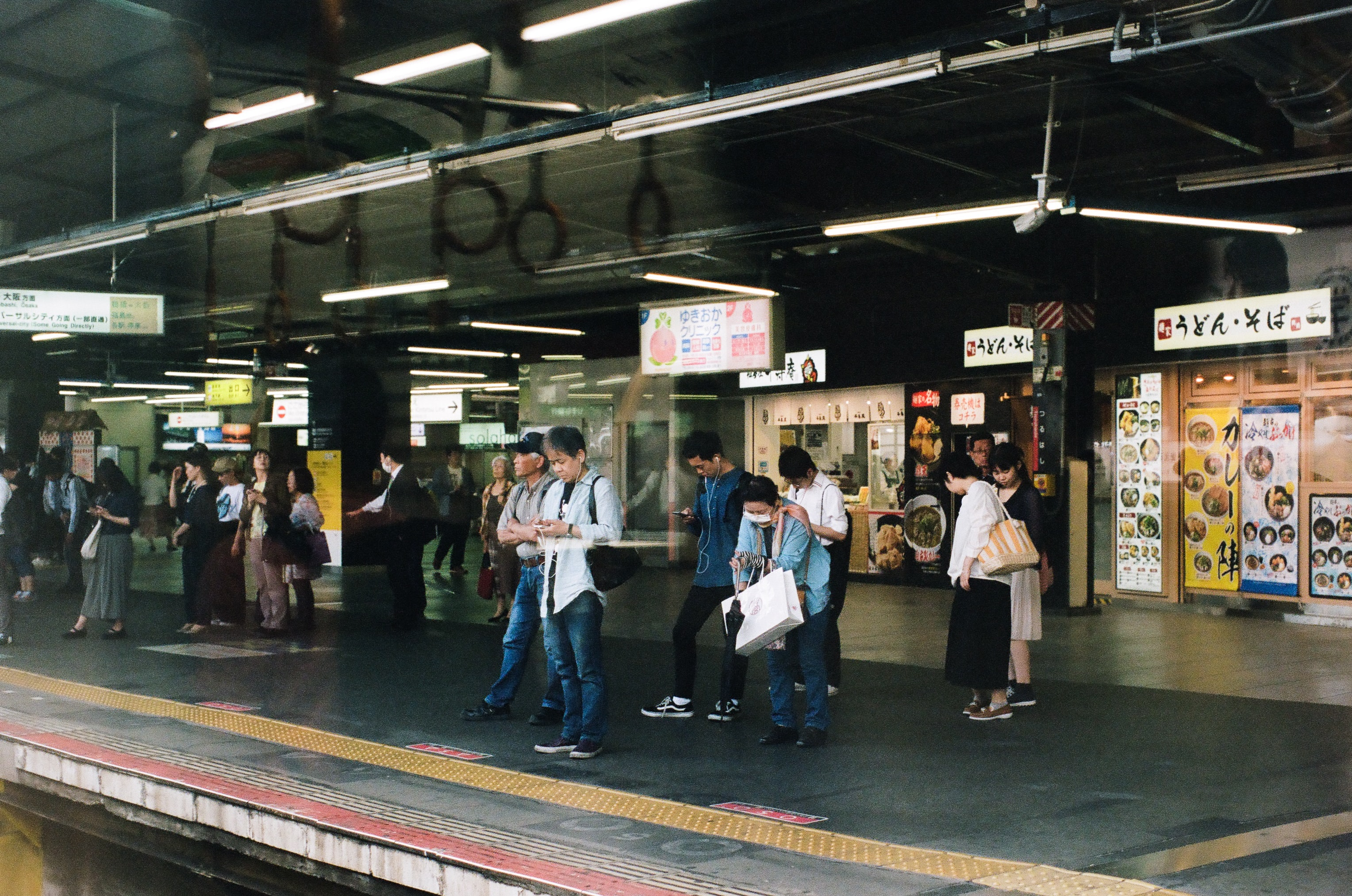 people standing near rails while waiting for train