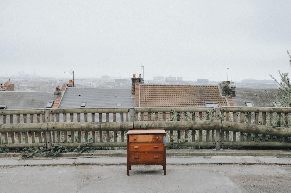 brown wooden dresser near brown fence during daytime