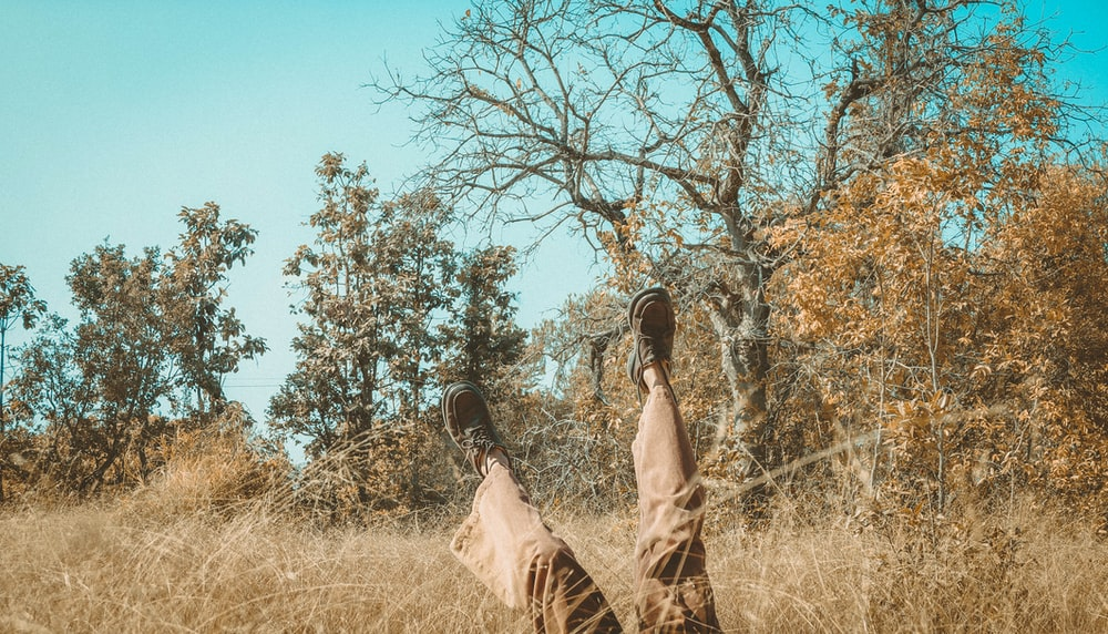 person raises both feet while lying on brown grass