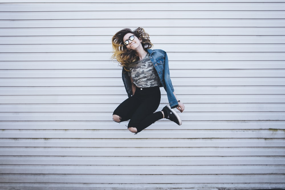 woman jumping in front of white concrete establishment