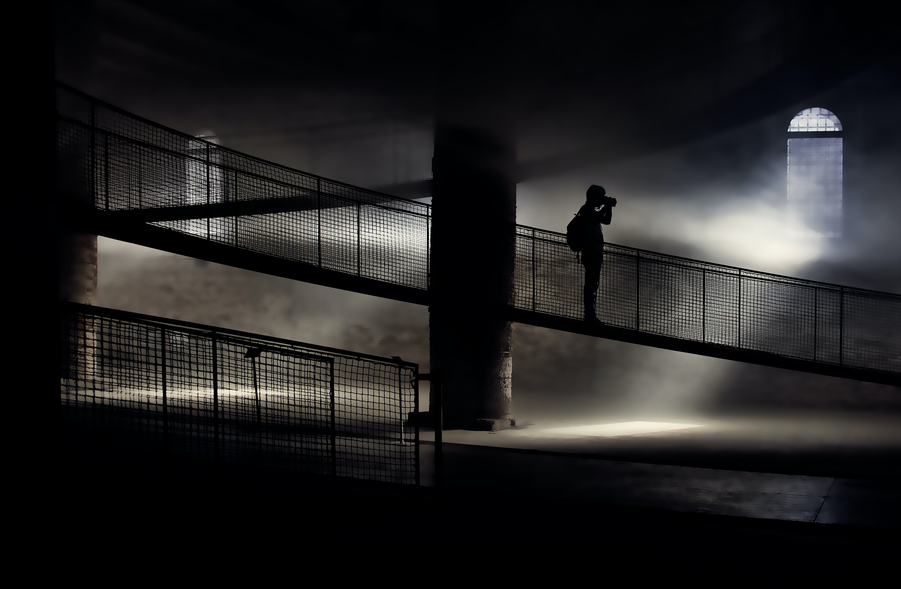 silhouette of person standing on bridge while taking photo