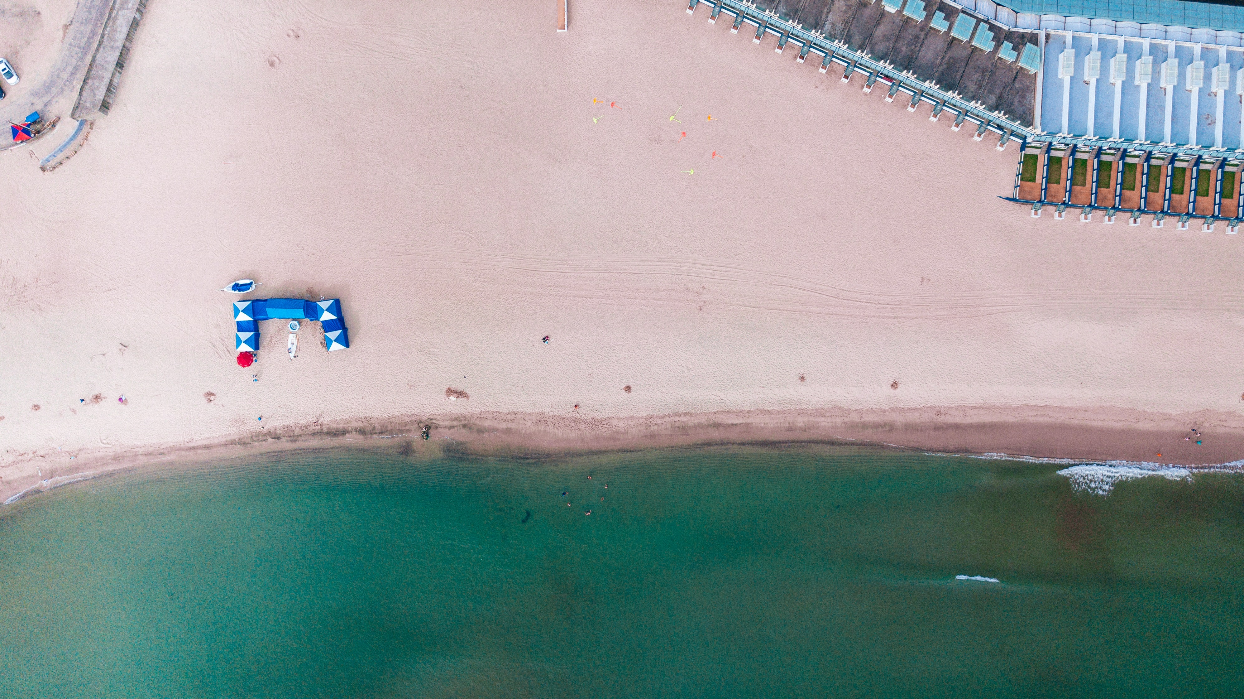 A drone shot of an empty sandy beach with a small blue pavilion