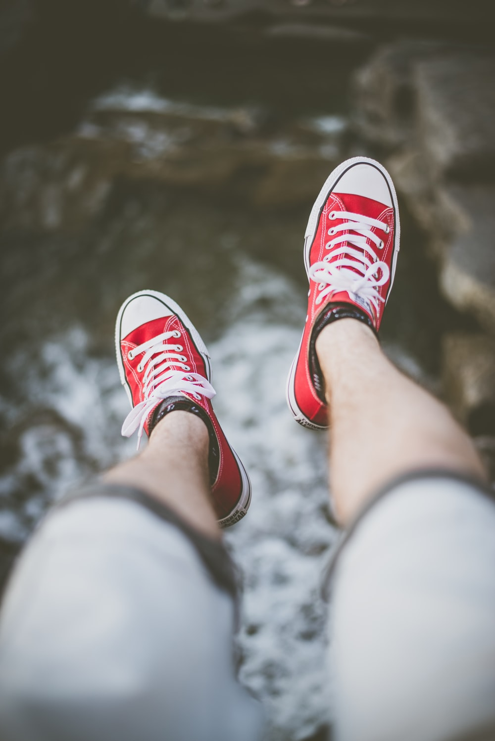 selective focus photography of person wearing red low-top sneakers over body of water