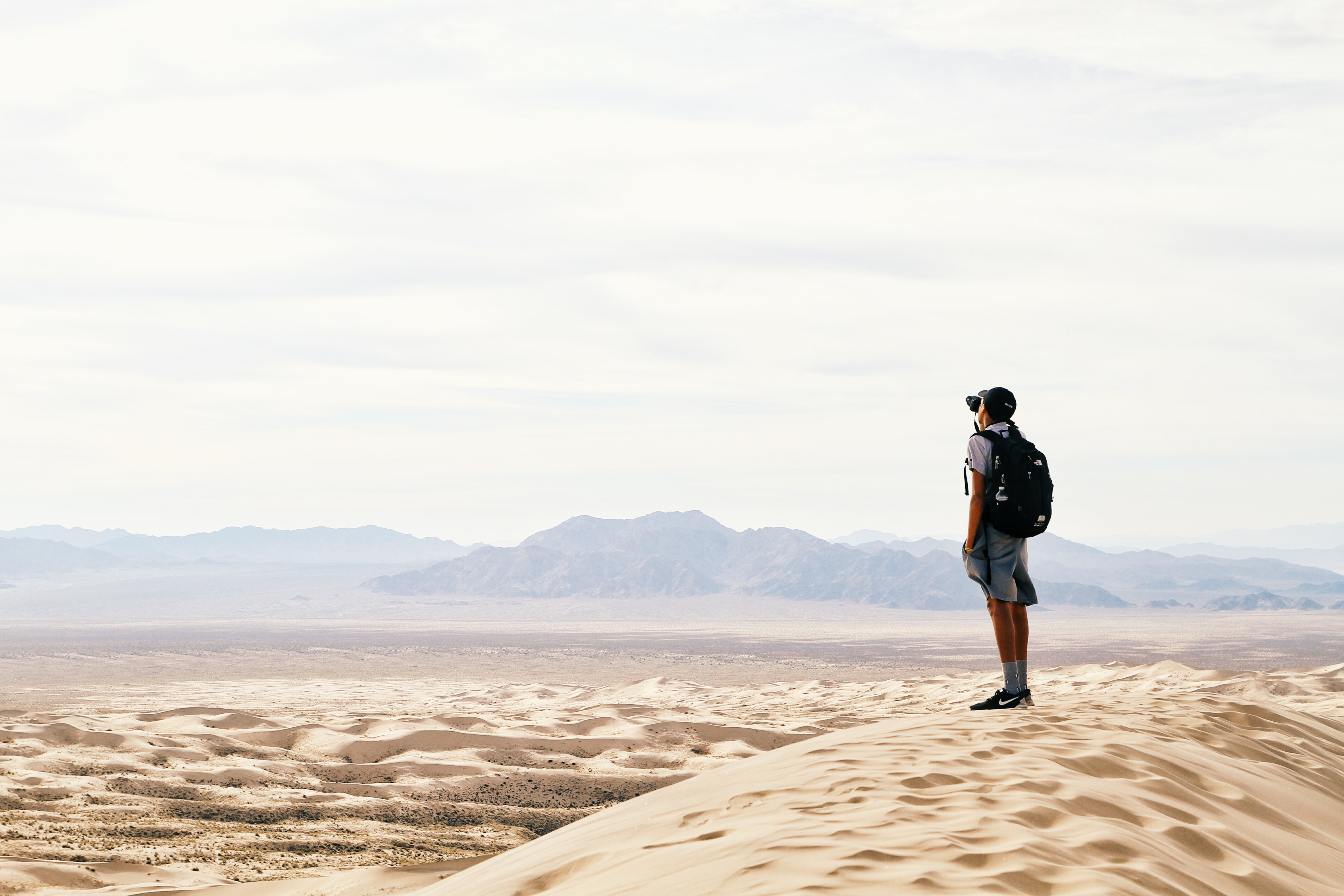A tourist with a camera standing on top of a sand dune in a desert
