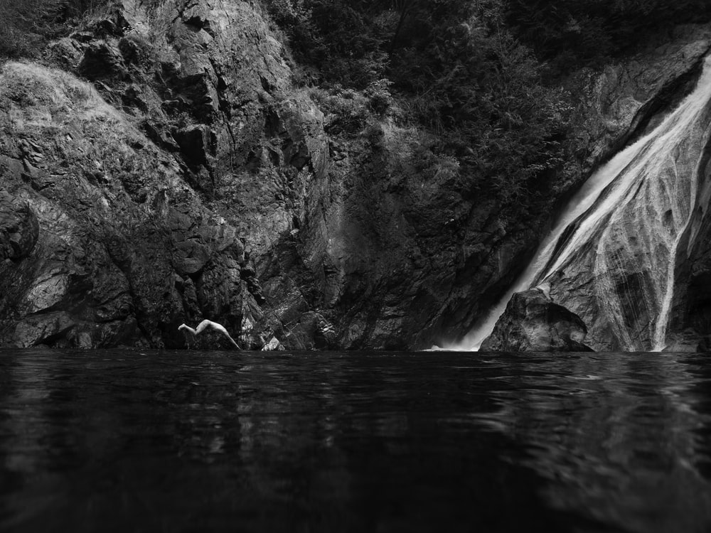 grayscale photography of flowing waterfall