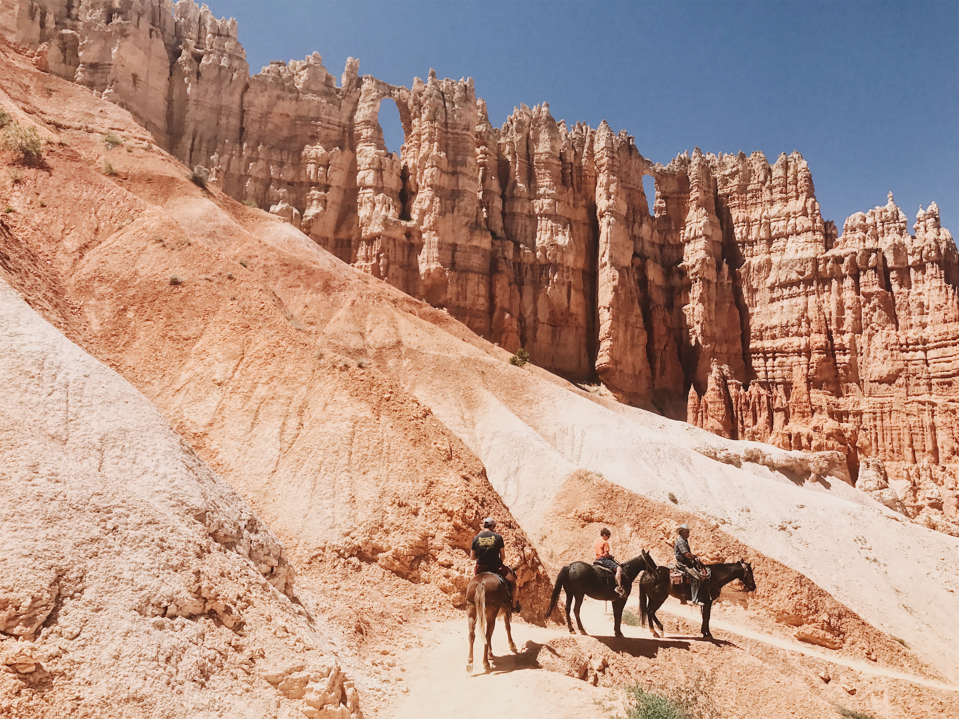 Three horse riders going down a steep slope under red sandstone outcroppings