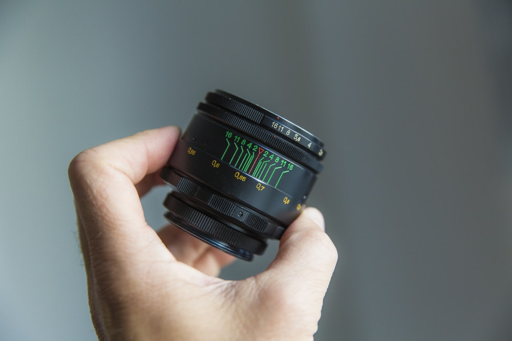 person holding black camera lens