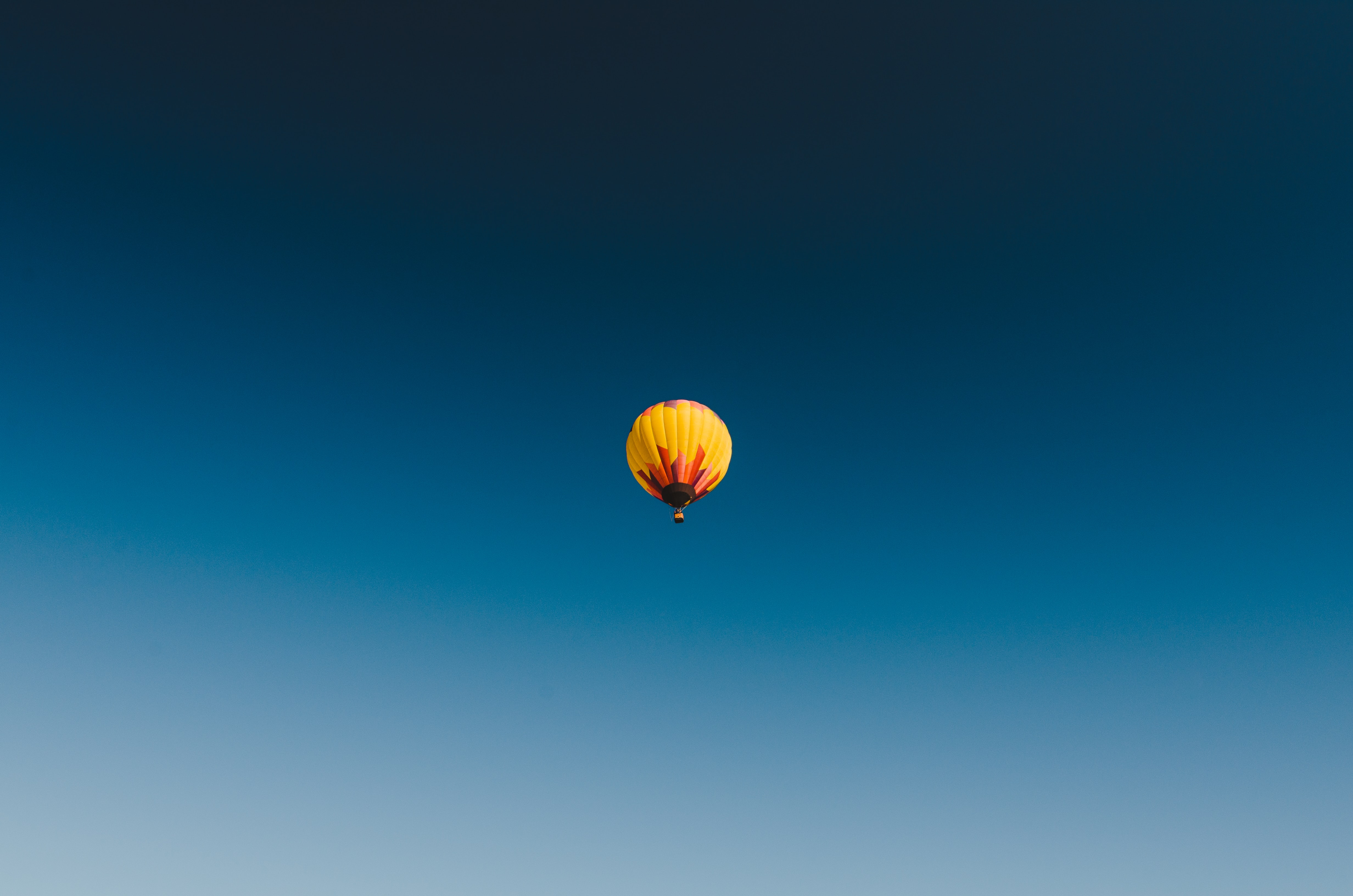 A solitary orange and yello hot air balloon floating in the sky at the Sonoma County Hot Air Balloon Classic