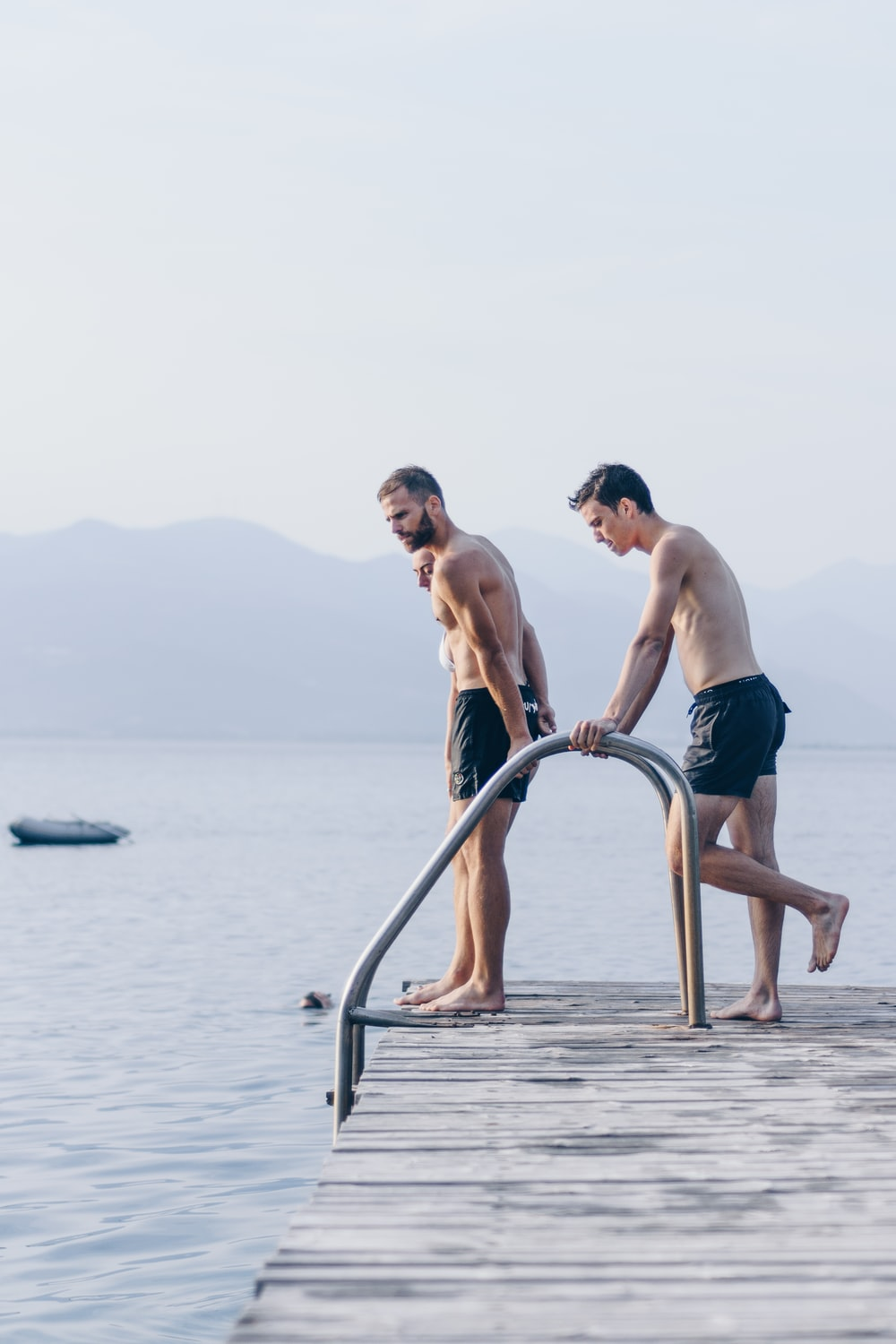 two men standing on brown dock near body of water during daytime