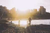 woman and children walking towards body of water during sunrise