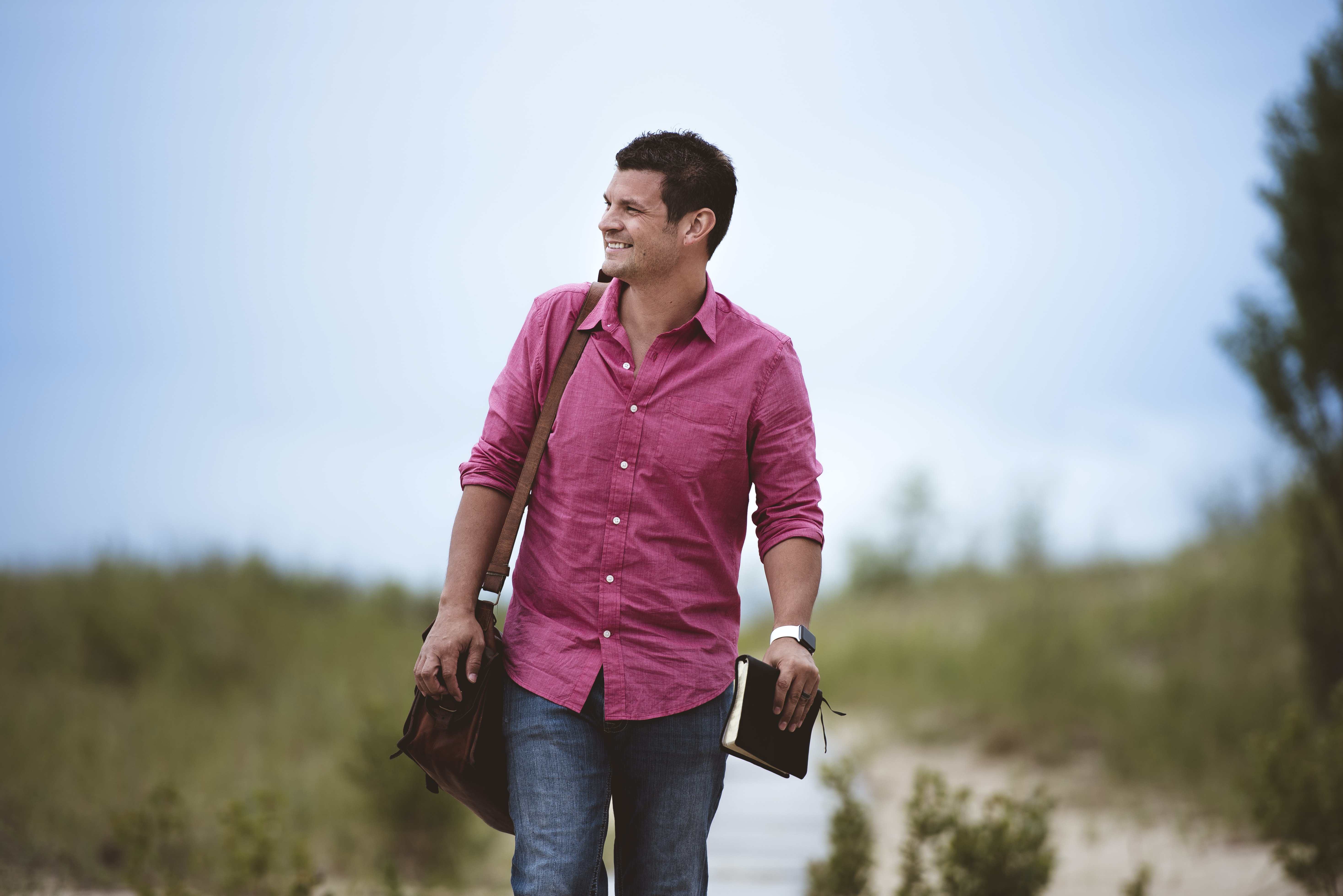 A man in a pink shirt with a leather bag and a book walking on a dirt path