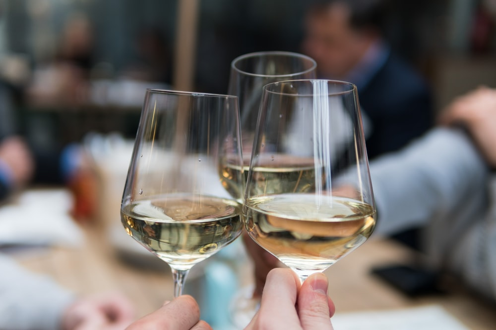 Three people clinking their wine glasses