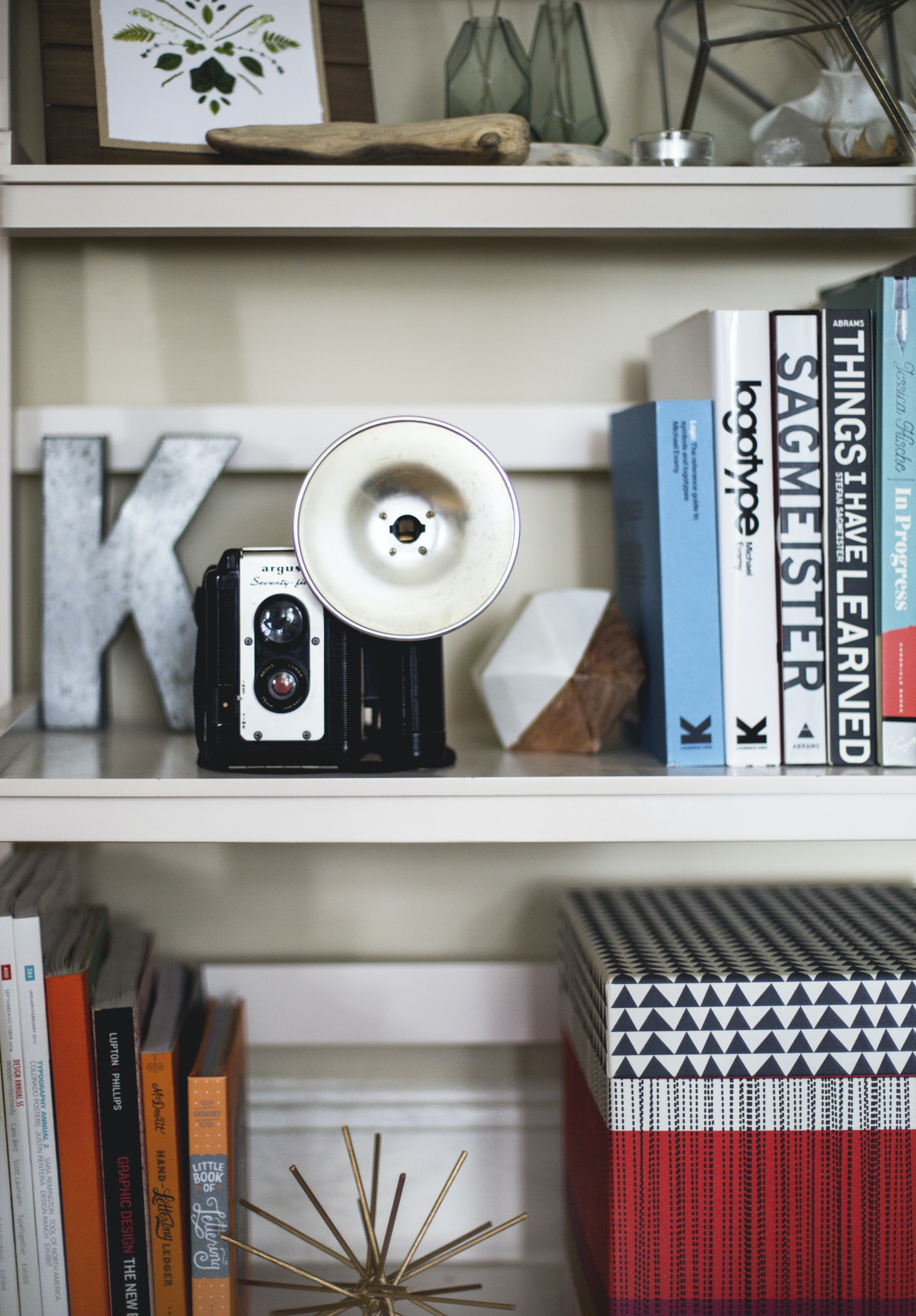 A vintage camera on a shelf lined with books and trinkets