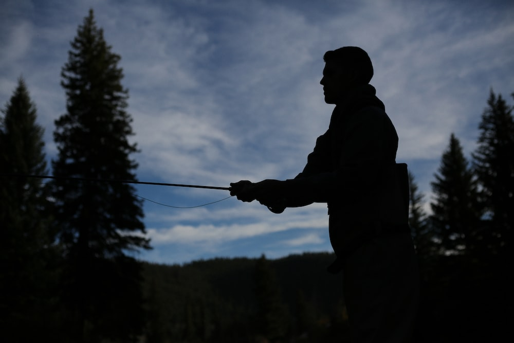silhouette of person fishing during nighttime