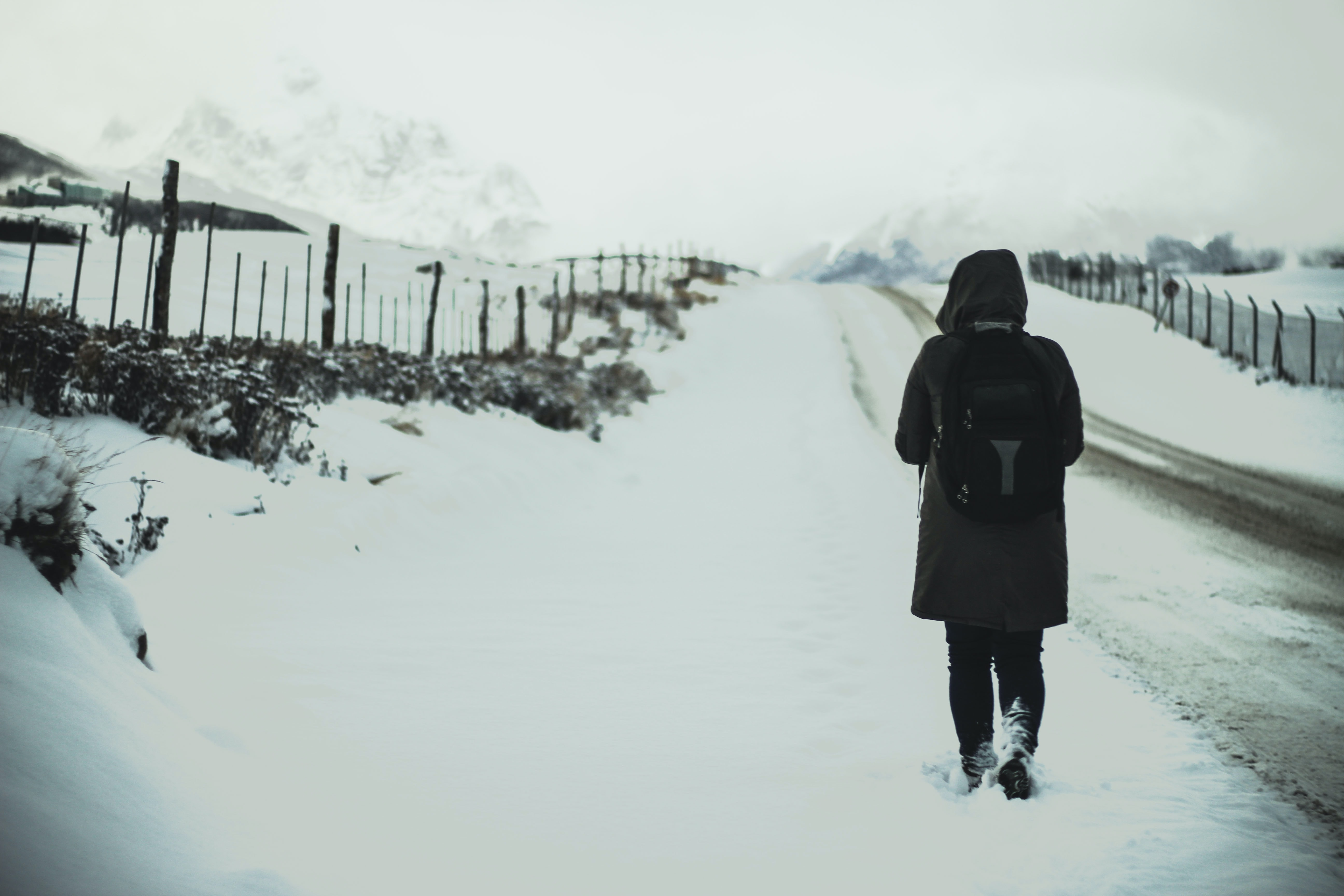 A person walking alongside a fence on a snow covered country road in Ushuaia in Argentina