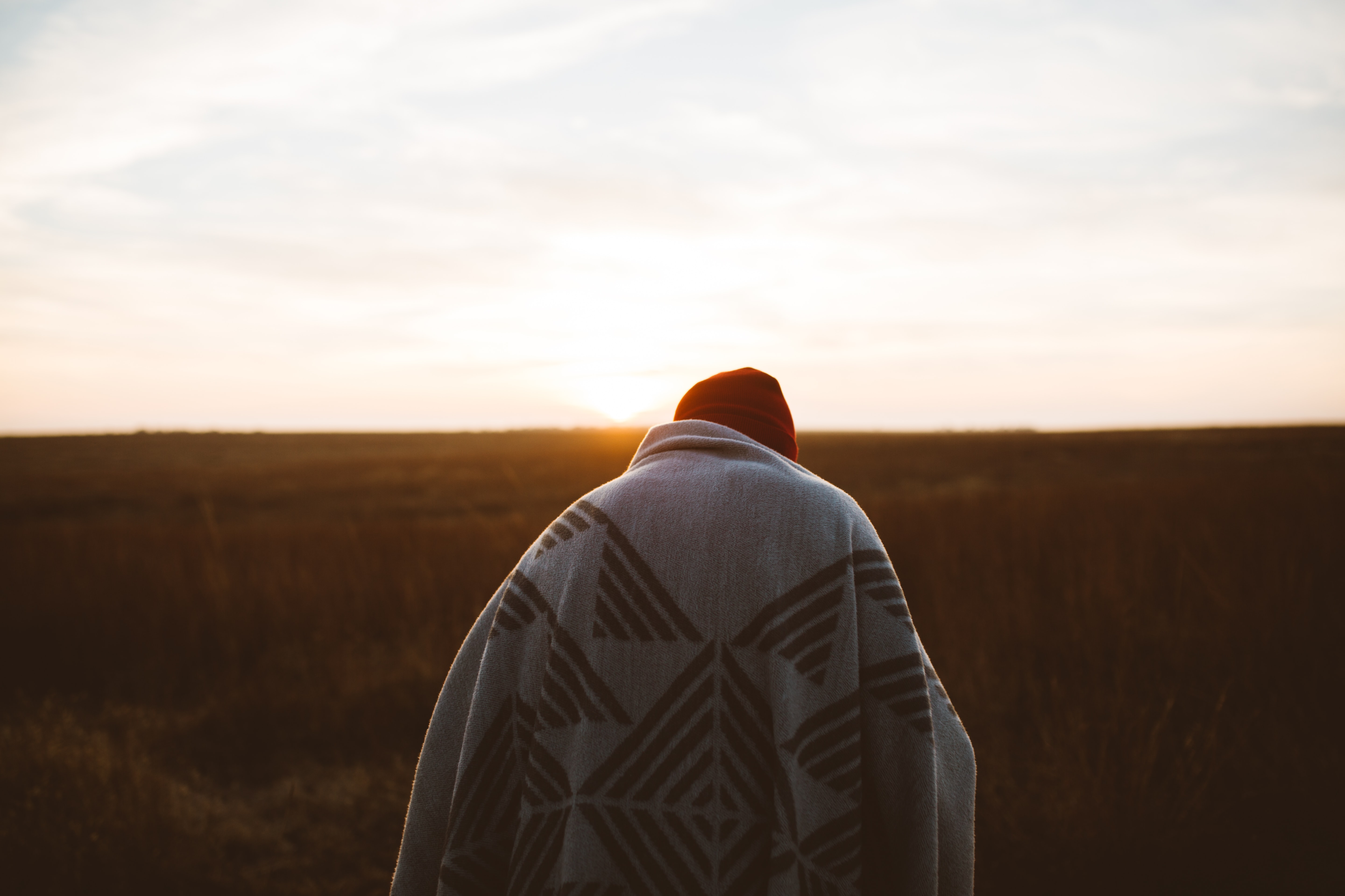 A person standing in a field at sunset, wrapped in a blanket and wearing a hat at sunset