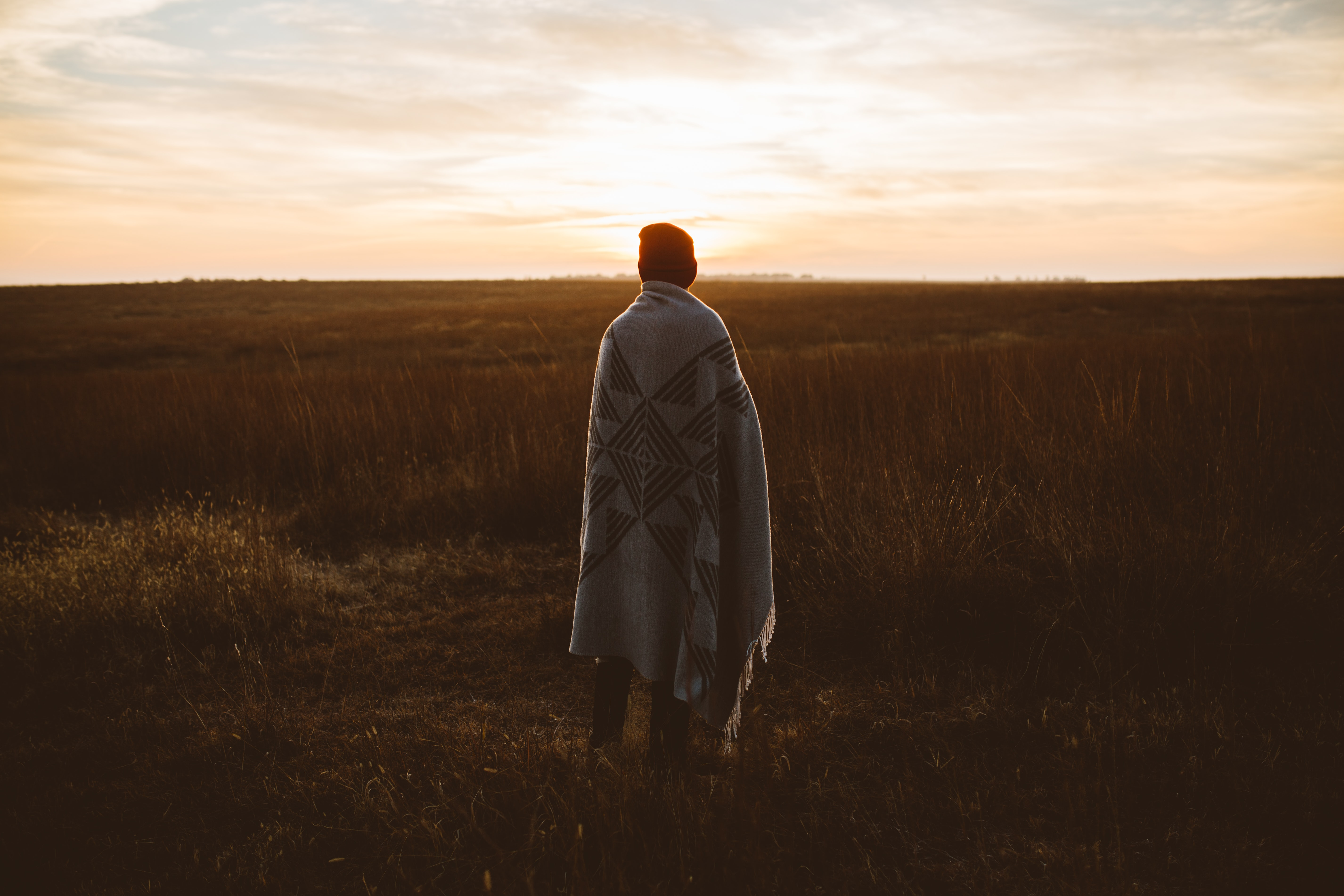 person cover in robe standing in front of grass field
