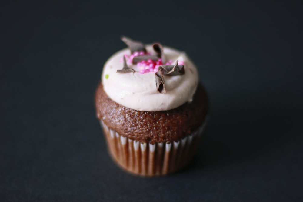 chocolate cupcake with white icing and grated chocolate