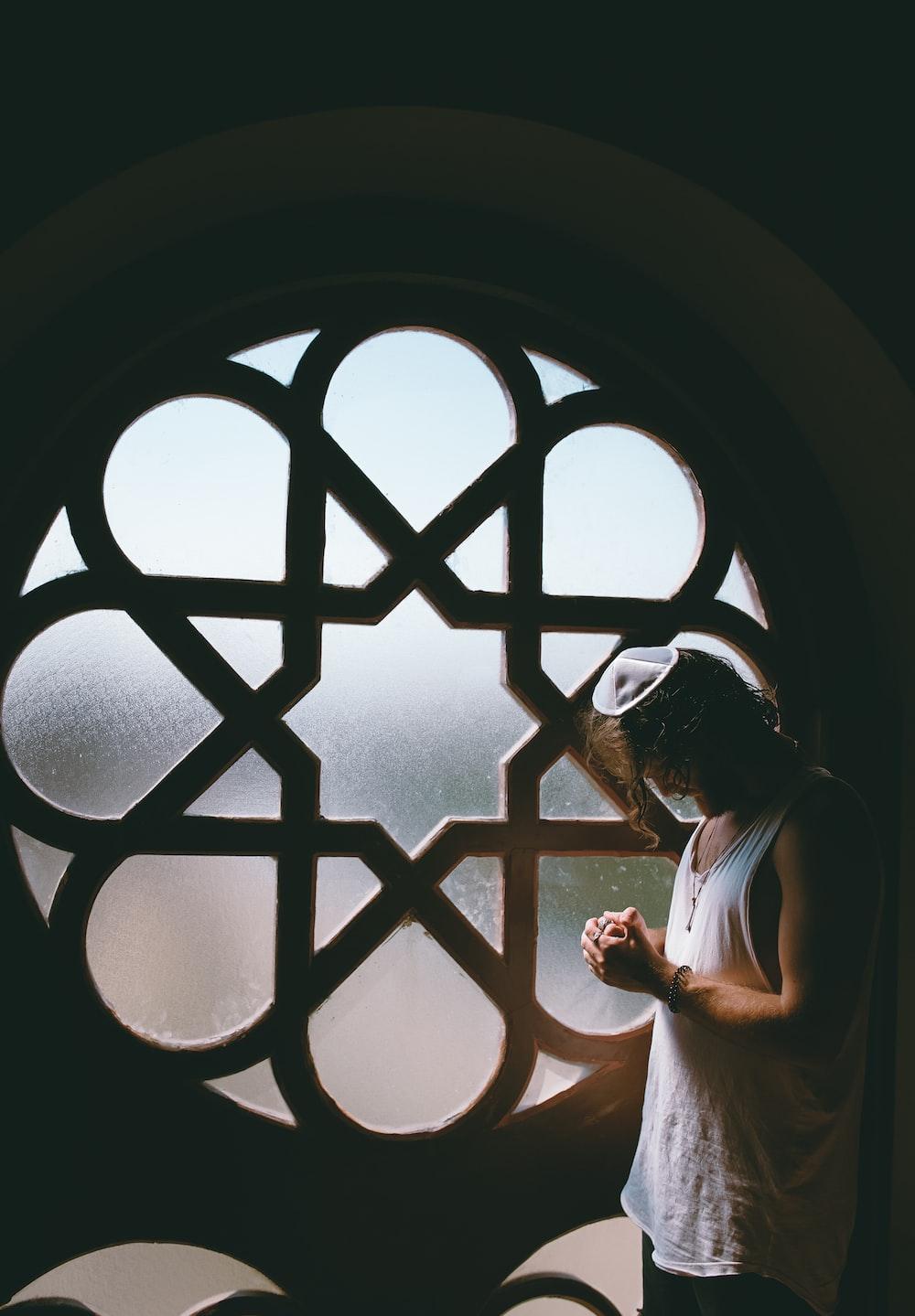 man in white tank top beside glass window