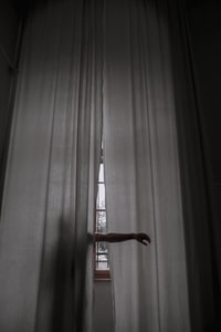 person standing beside the curtain and rising their arms