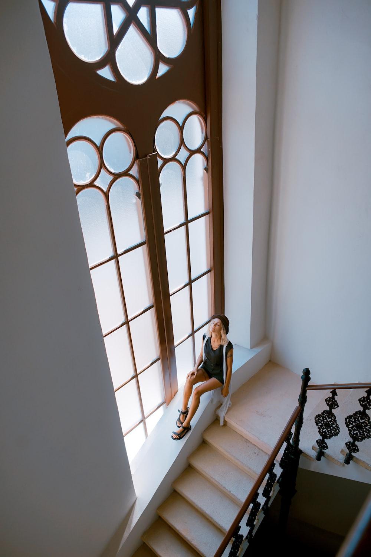 woman sitting besides stair window