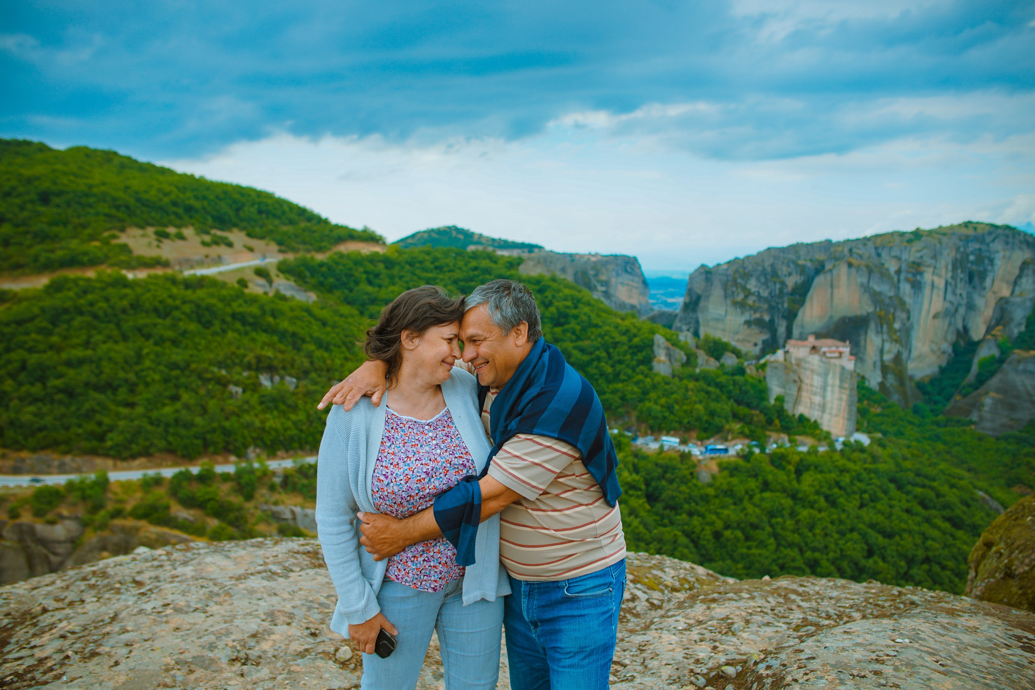 An older couple in a loving embrace above a valley in Meteora