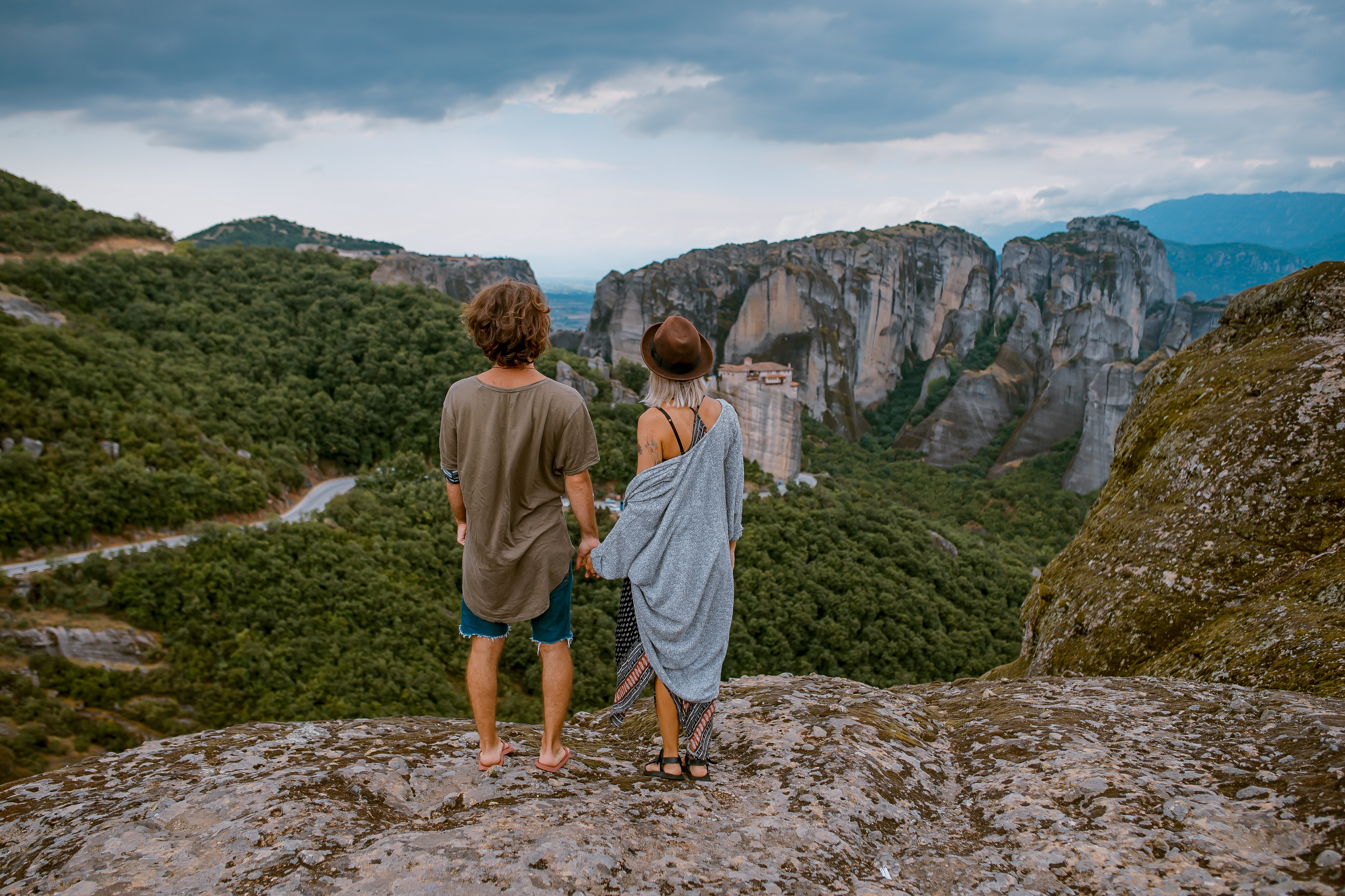 Bohemian couple looks away down from a mountain's crest to the valley below
