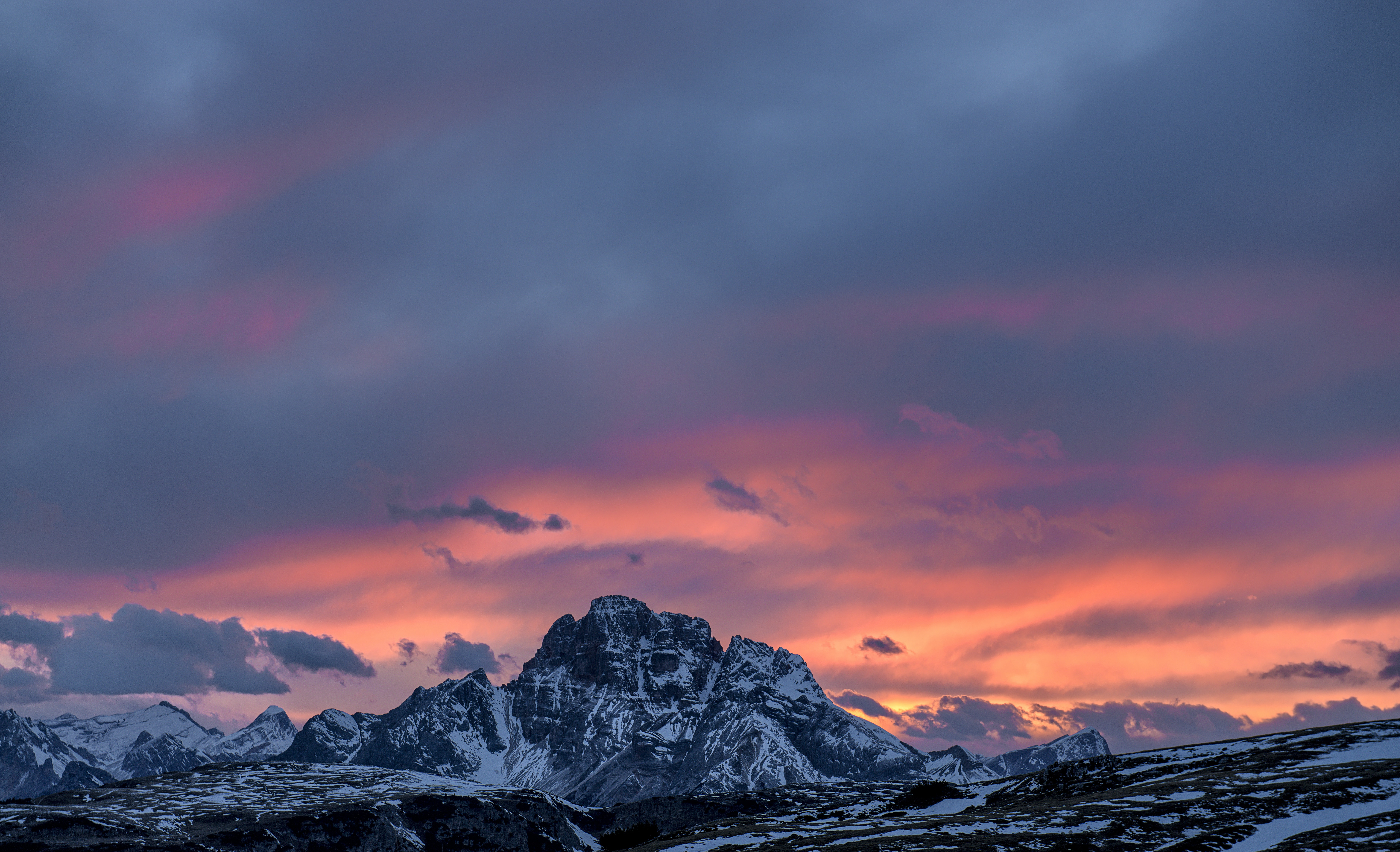 The snow covered Dolomites mountain range during dusk-or-dawn with background of cloudy, pink sky
