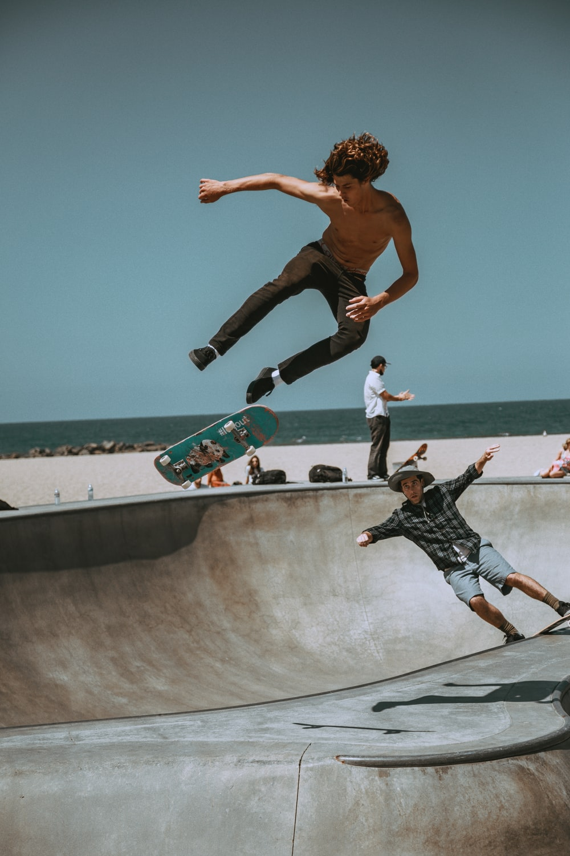 two men skateboarding on bowl ramp