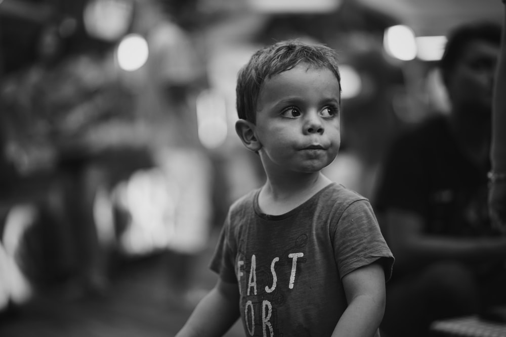 grayscale photo of boy in crew-neck shirt