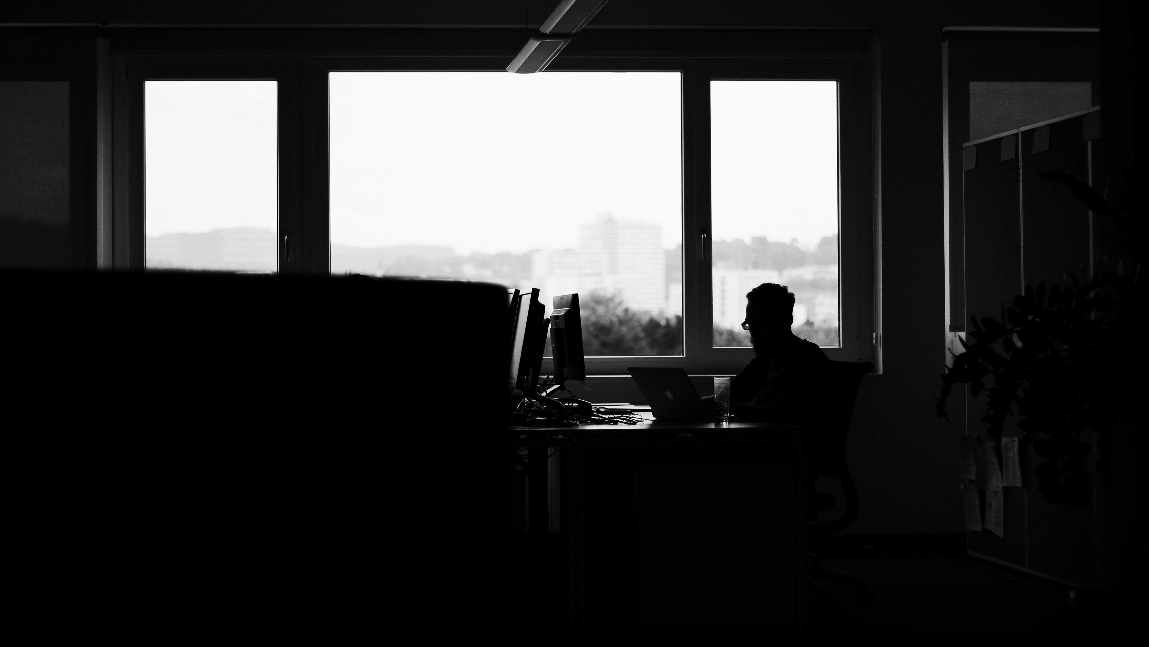 A dim shot of a man sitting at a desk with a laptop near a window