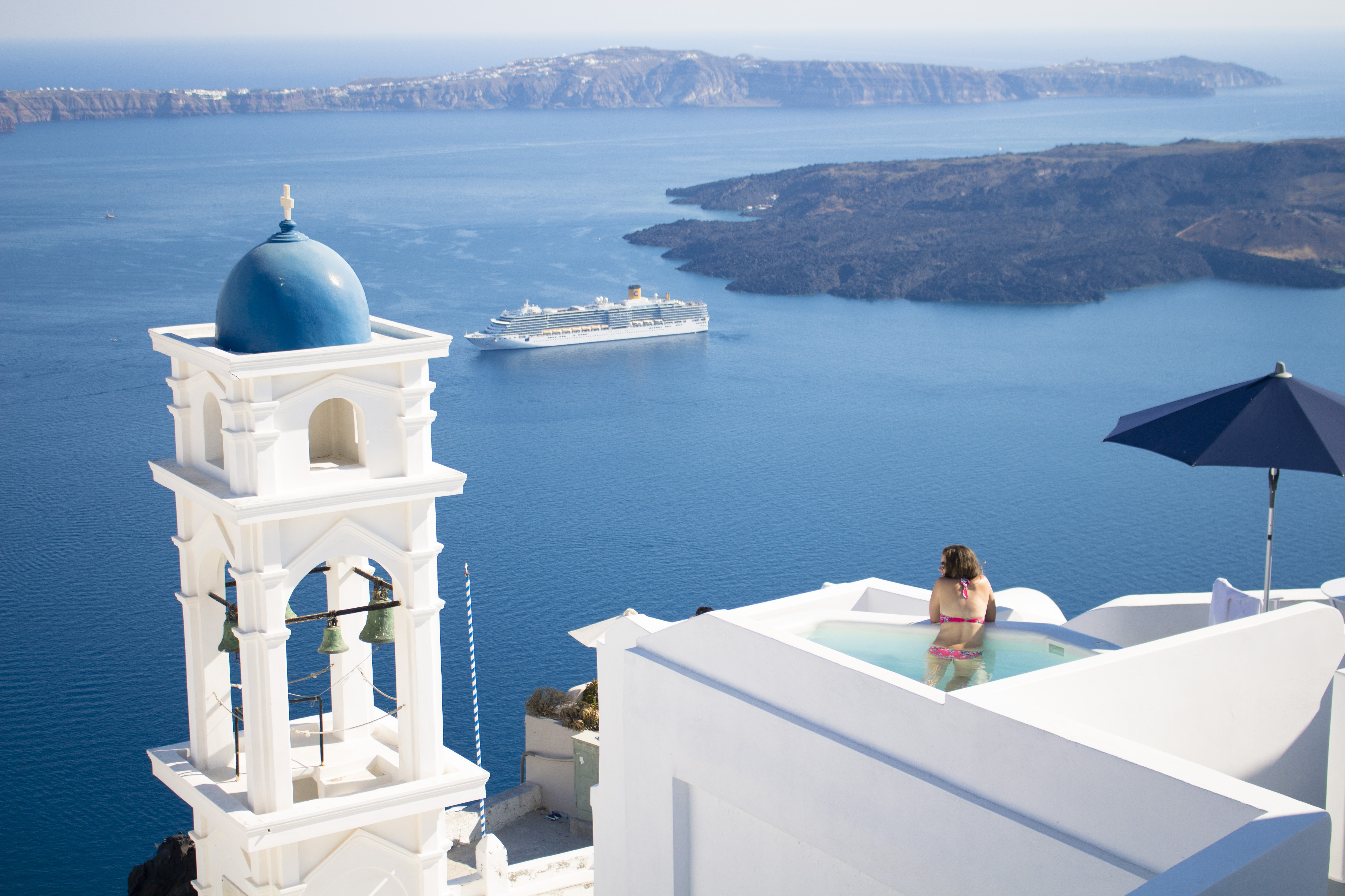 A woman in a swimsuit stands up in a tiny pool at the top of a white building in a classic Greek seaside town
