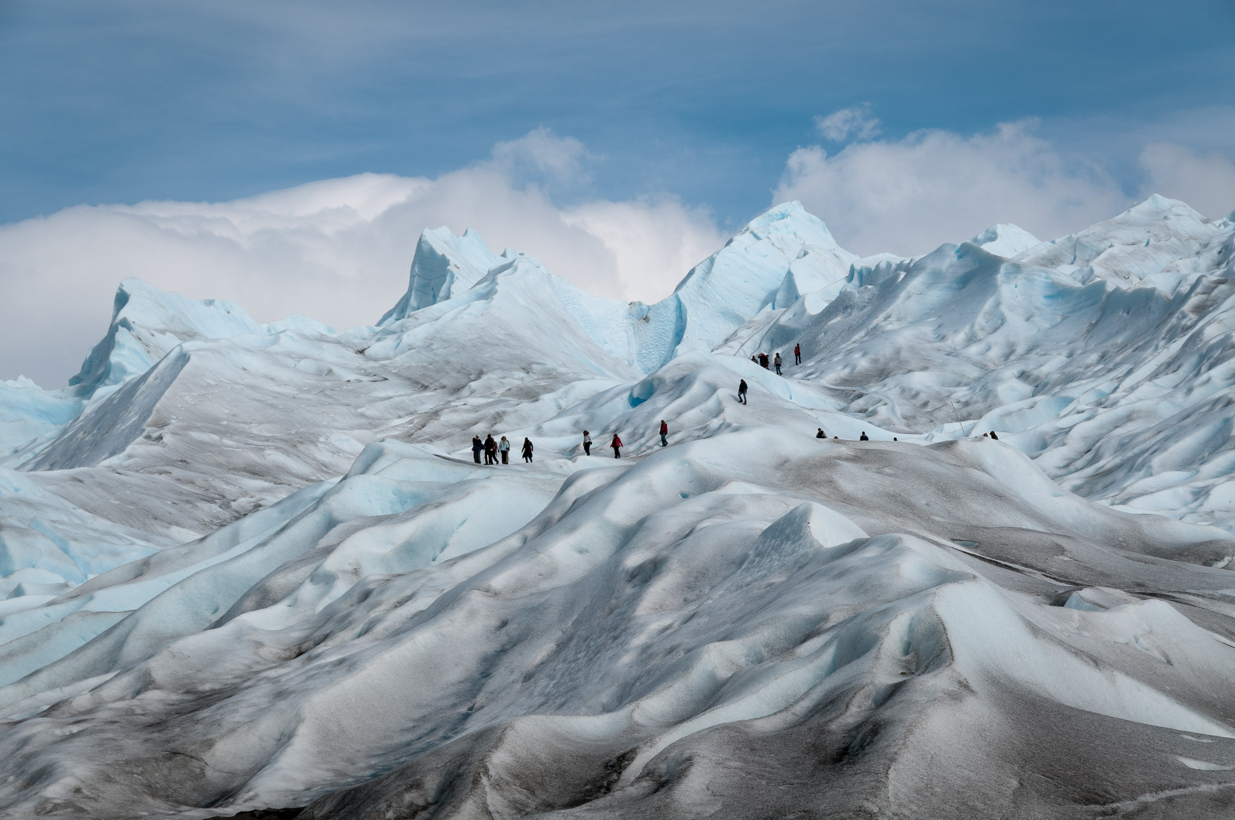 A group of trekkers climbing snow filled mountains with clear skies.