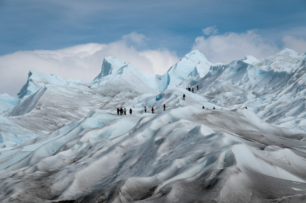 photo of people on top of snow-covered mountain