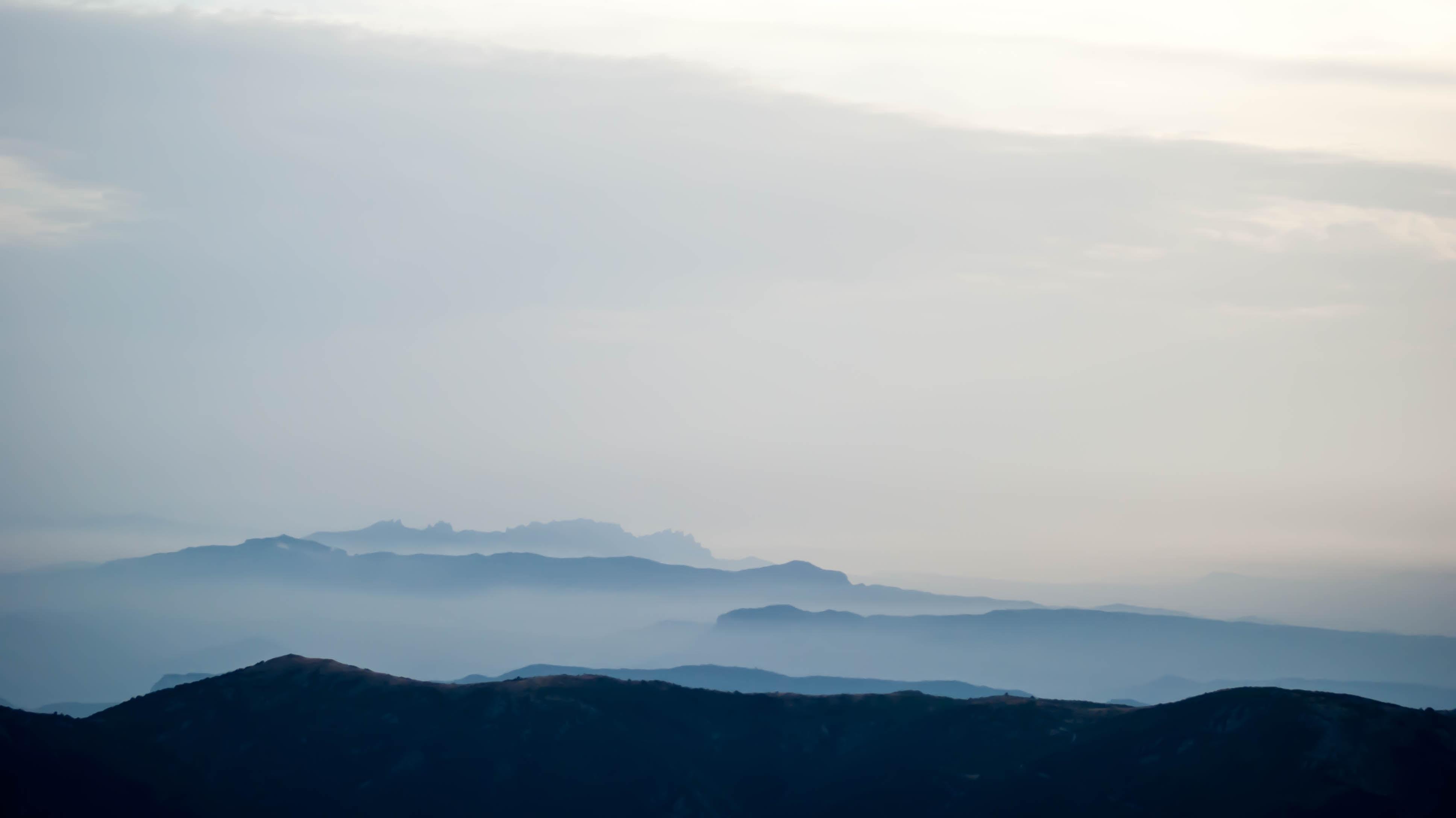 Hazy silhouettes of mountain ridges on a foggy day