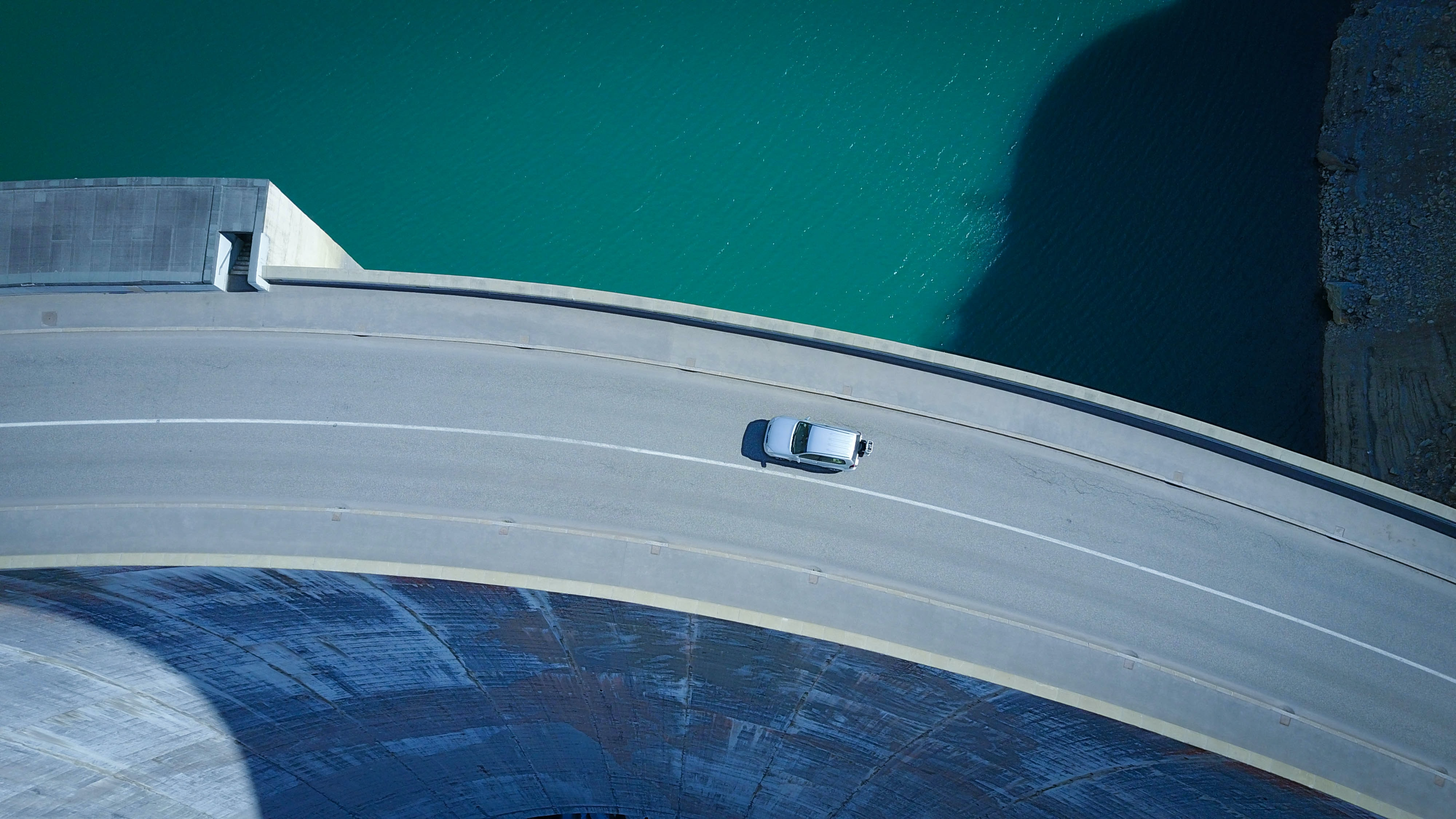 An aerial shot of a car driving along a curve in a road on a tall dam
