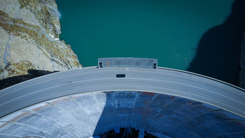 aerial view of concrete road beside body of water