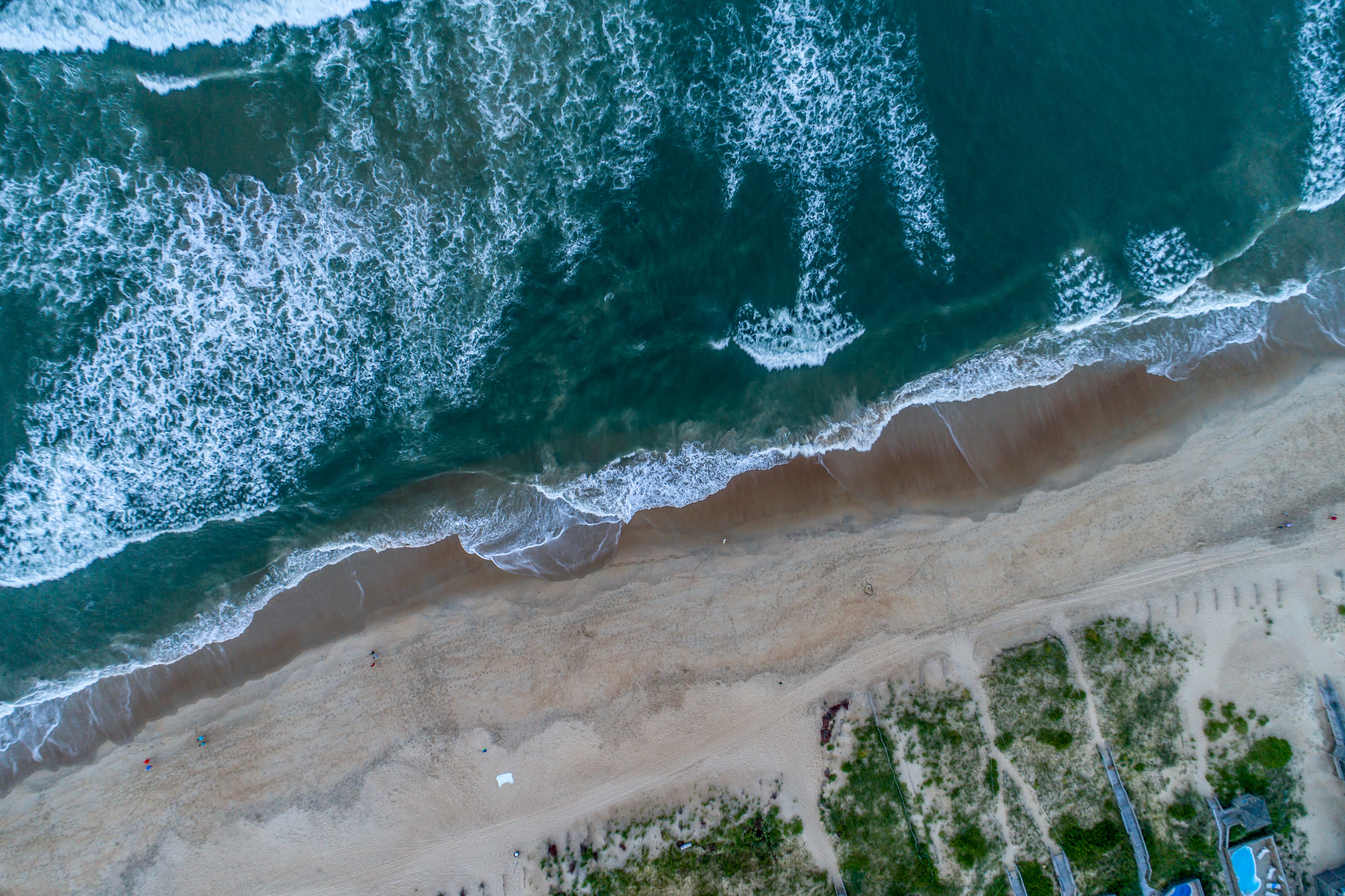 Drone aerial view of the ocean washing on the sand beach shore at Nags Head, North Carolina, United States