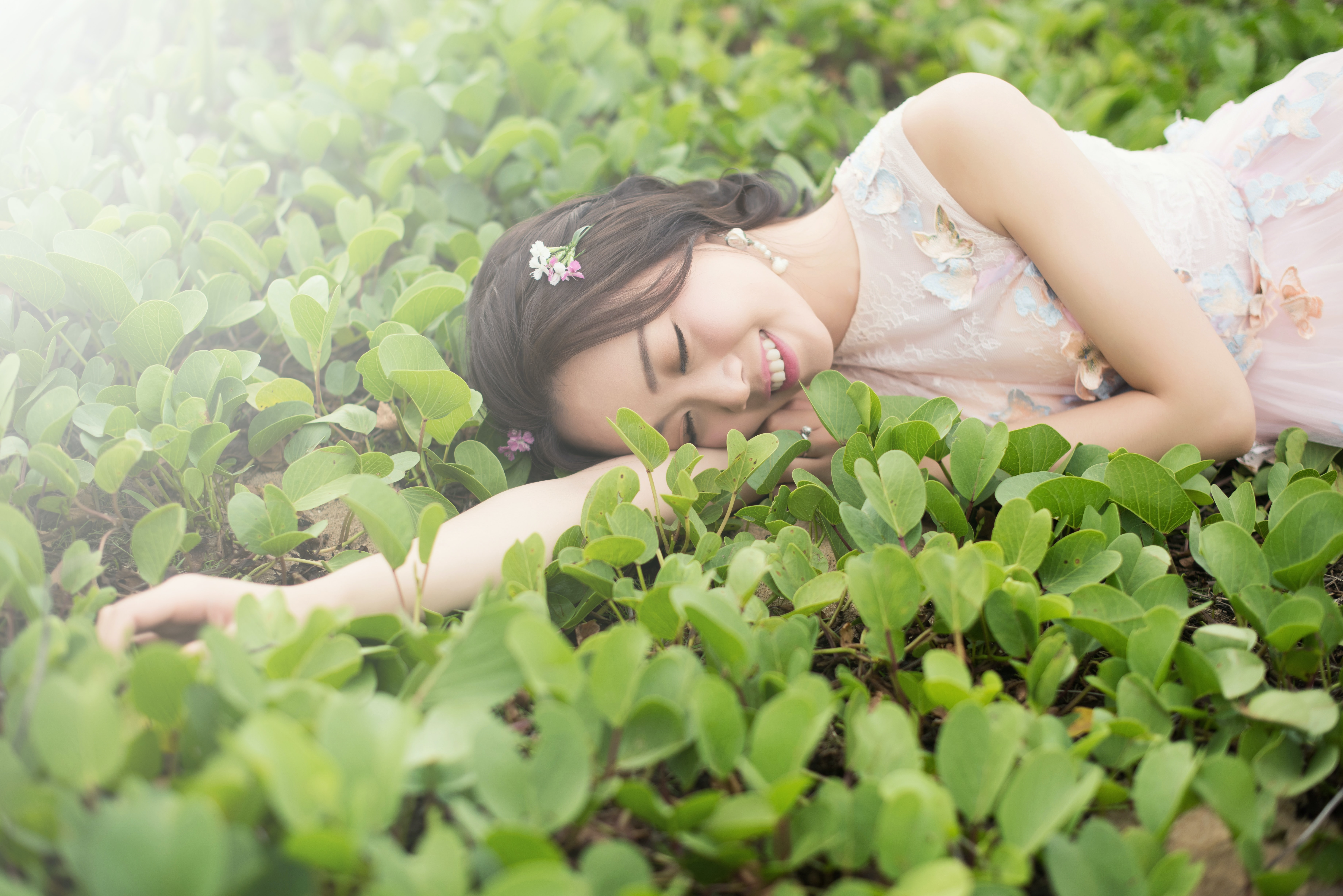 An Asian woman lying down in the grass smiling in a pretty pink dress