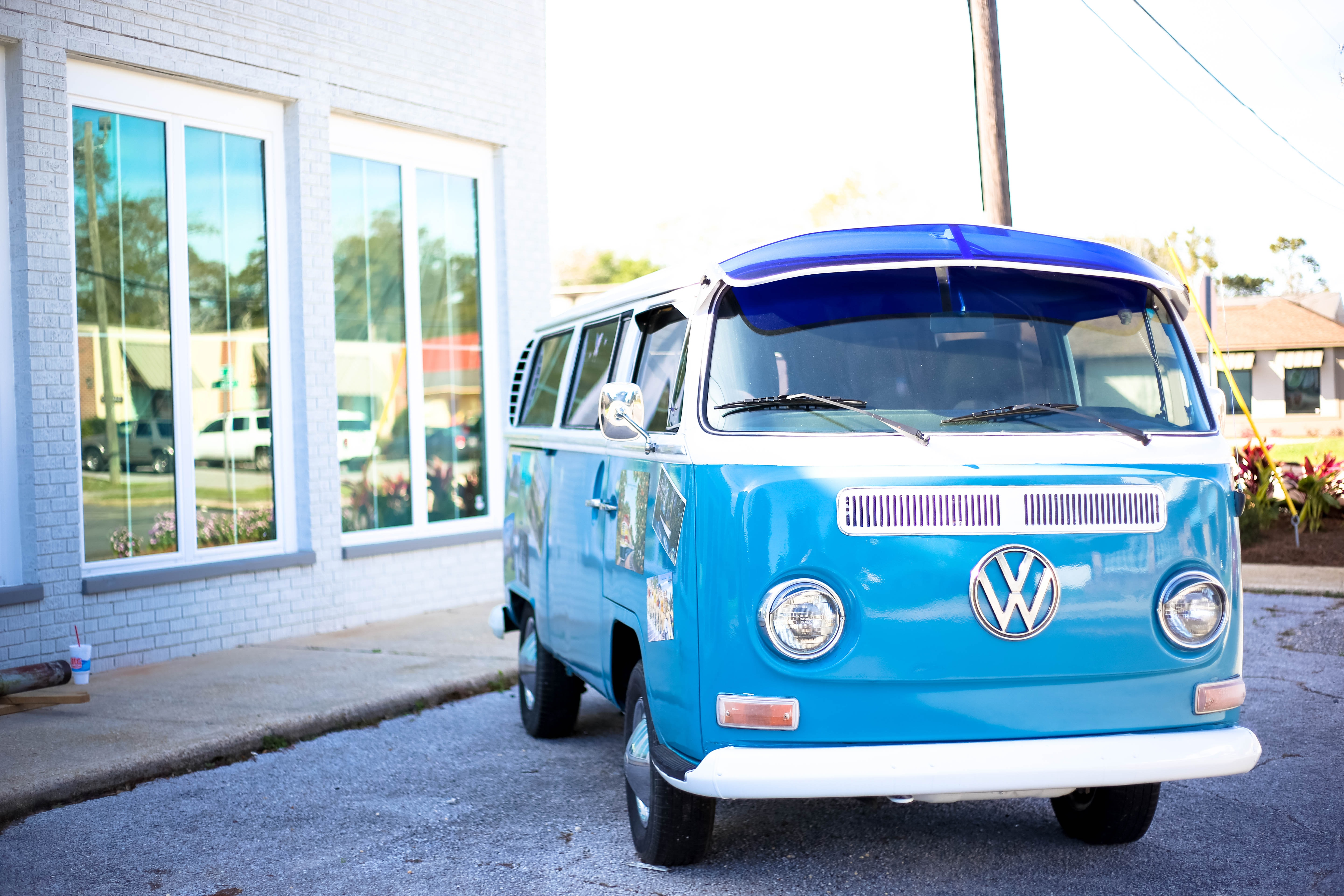 "Vintage blue VW van with ""VW"" logo parks in front of a building with reflective windows"