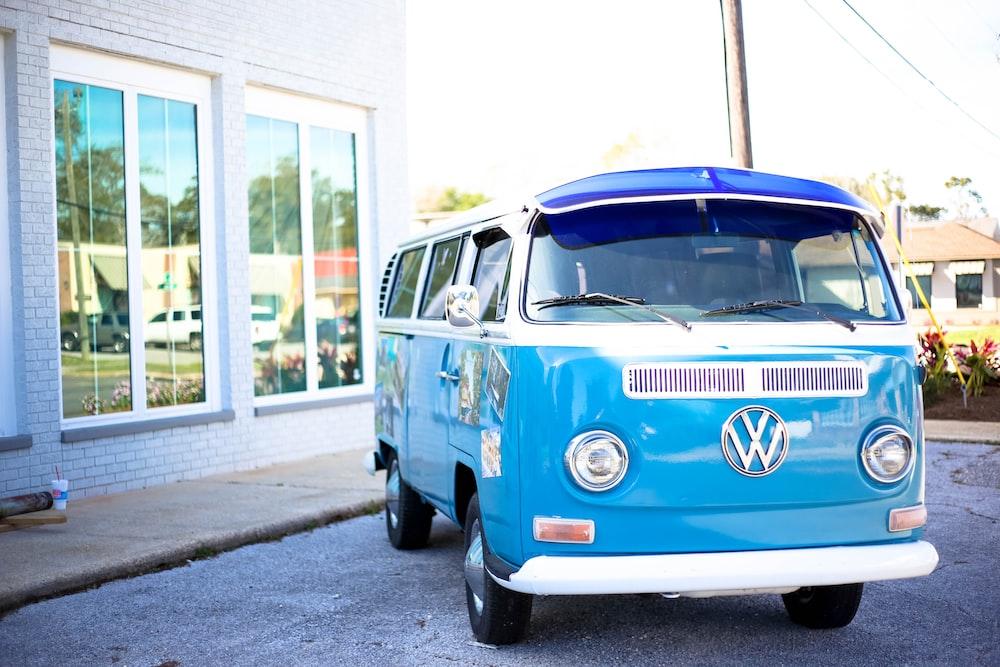 teal Volkswagen Samba in front of building
