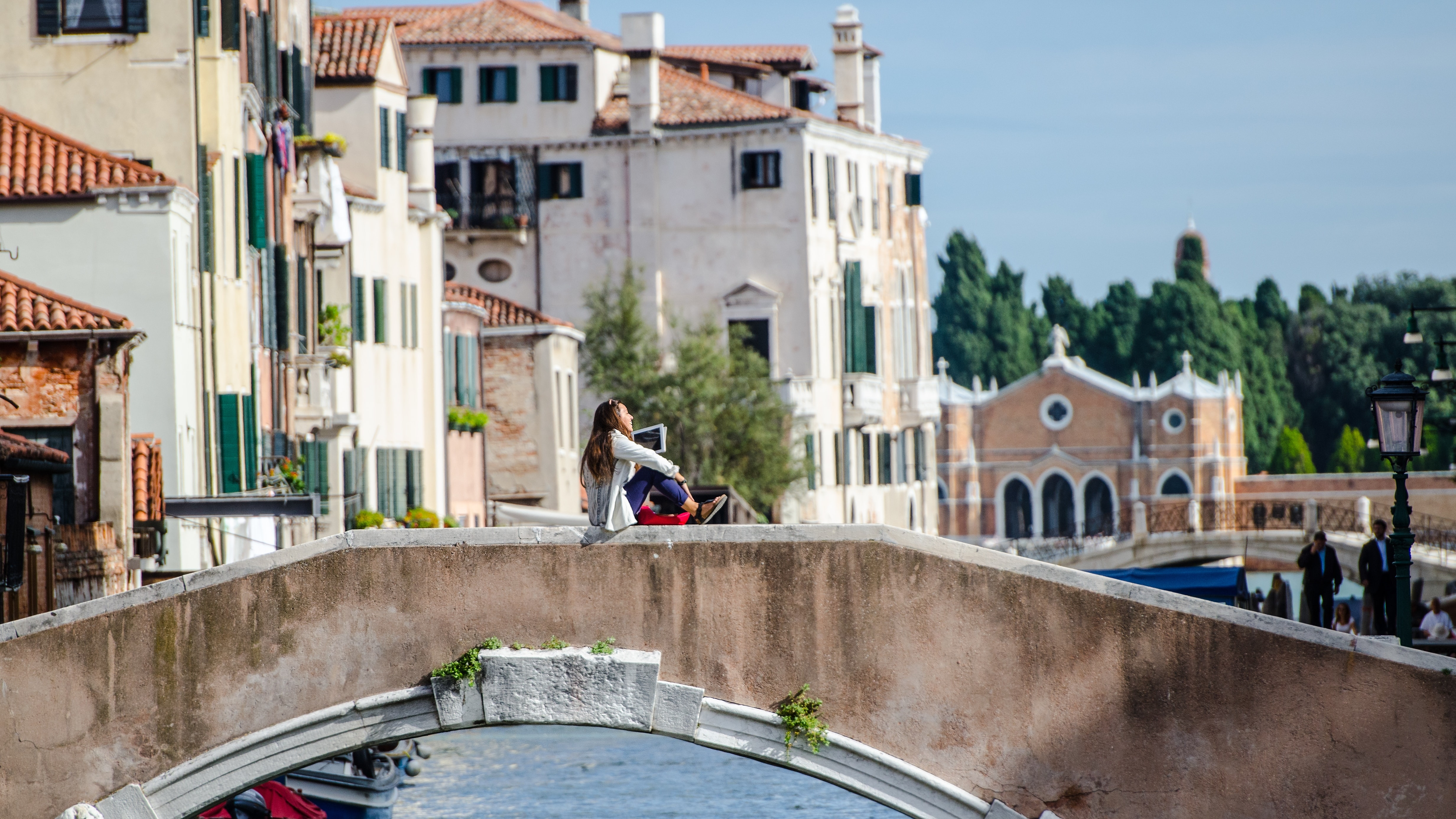 woman sitting on bridge rail over canal