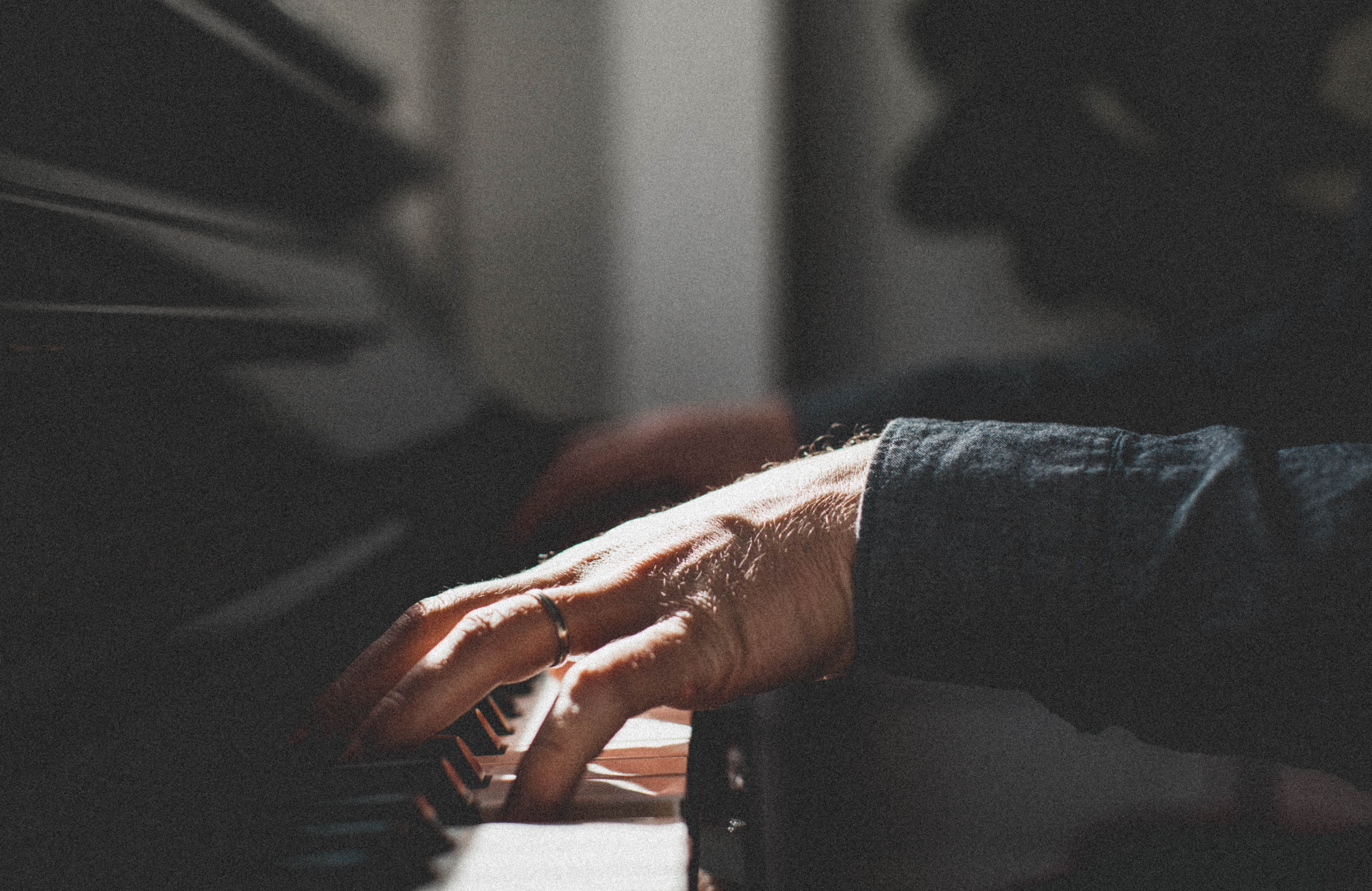 A grainy shot of a pianist's hands on the keyboard