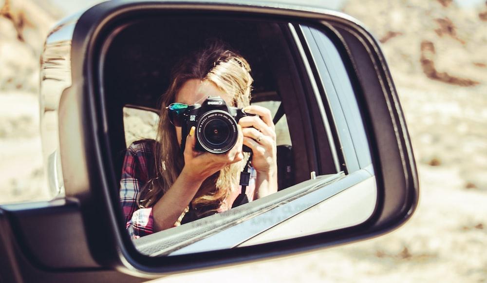 woman holding DSLR camera facing side mirror