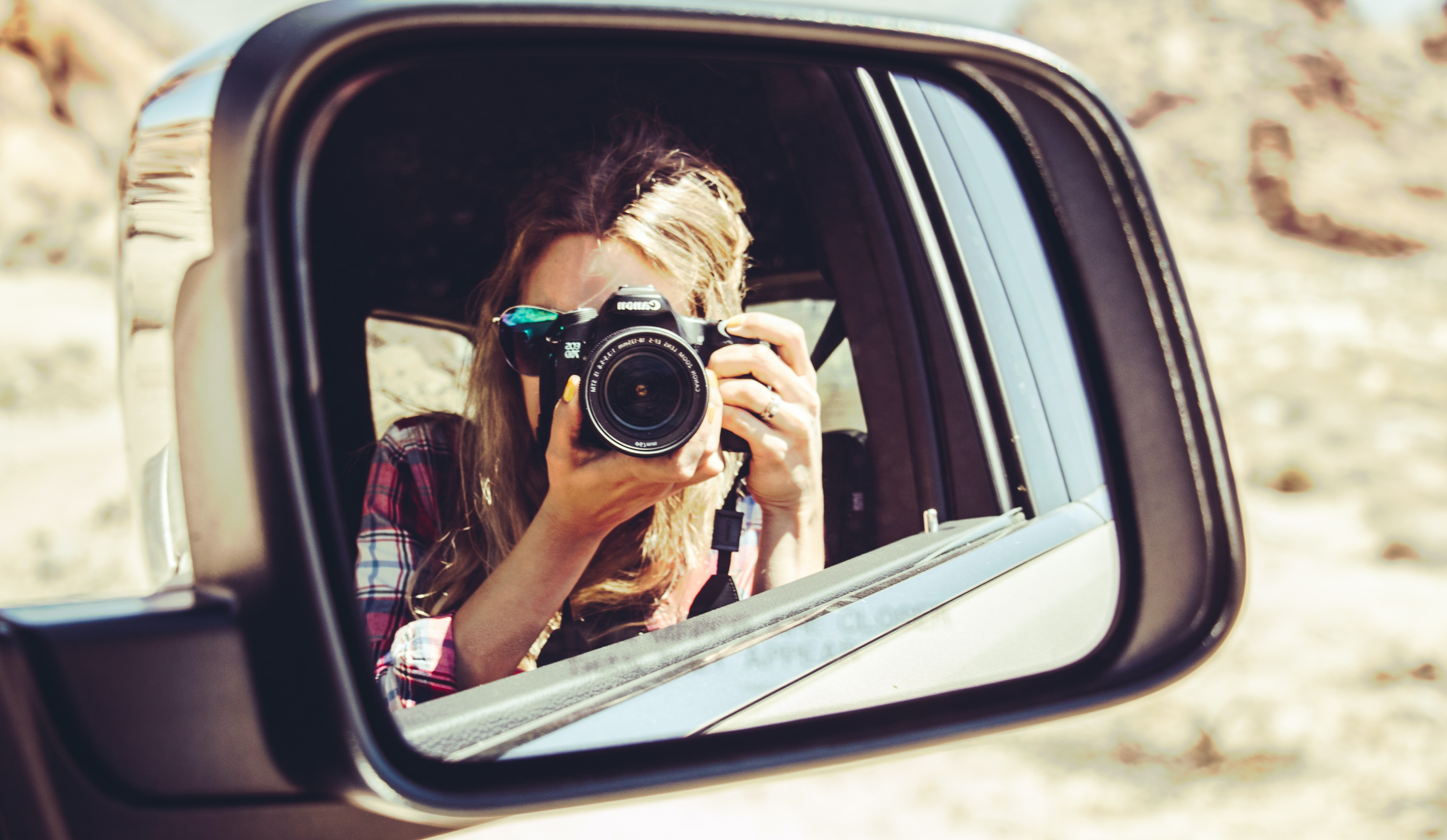 woman holding DSLR camera facing side mirror